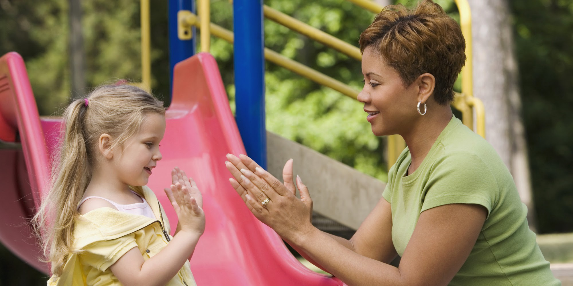 White child with long blond hair/pigtails playing paddycake with black women with short hair and green shirt on playground