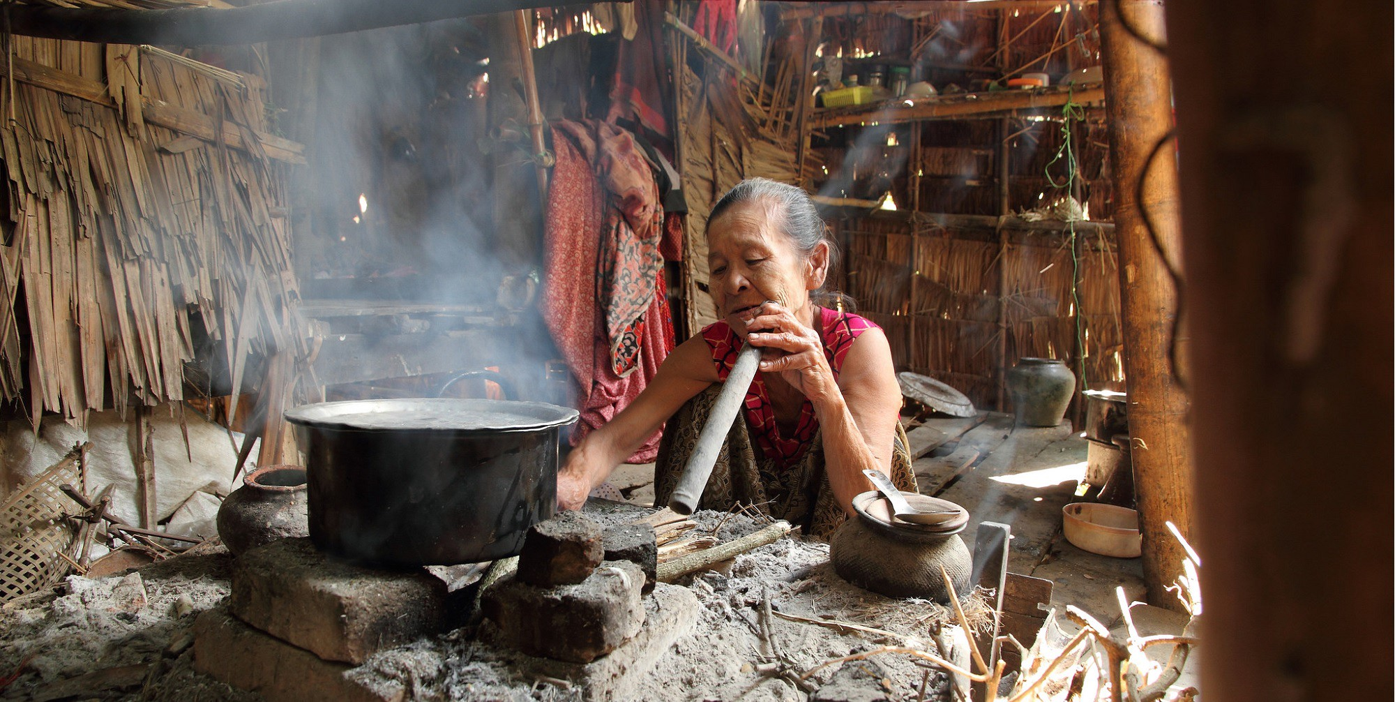 Woman cooking on a traditional stove