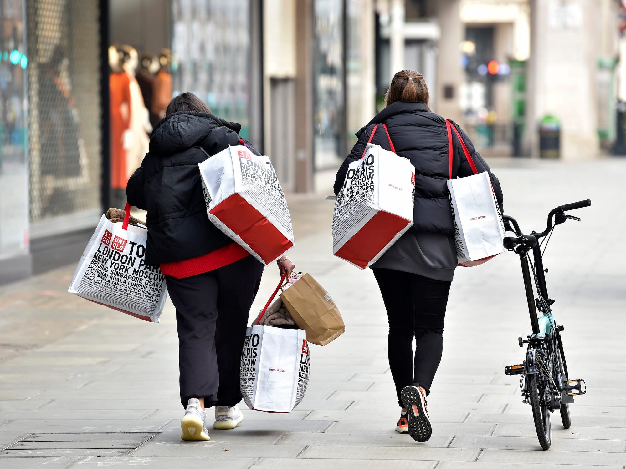 Individuals walking down the street with shopping bags.