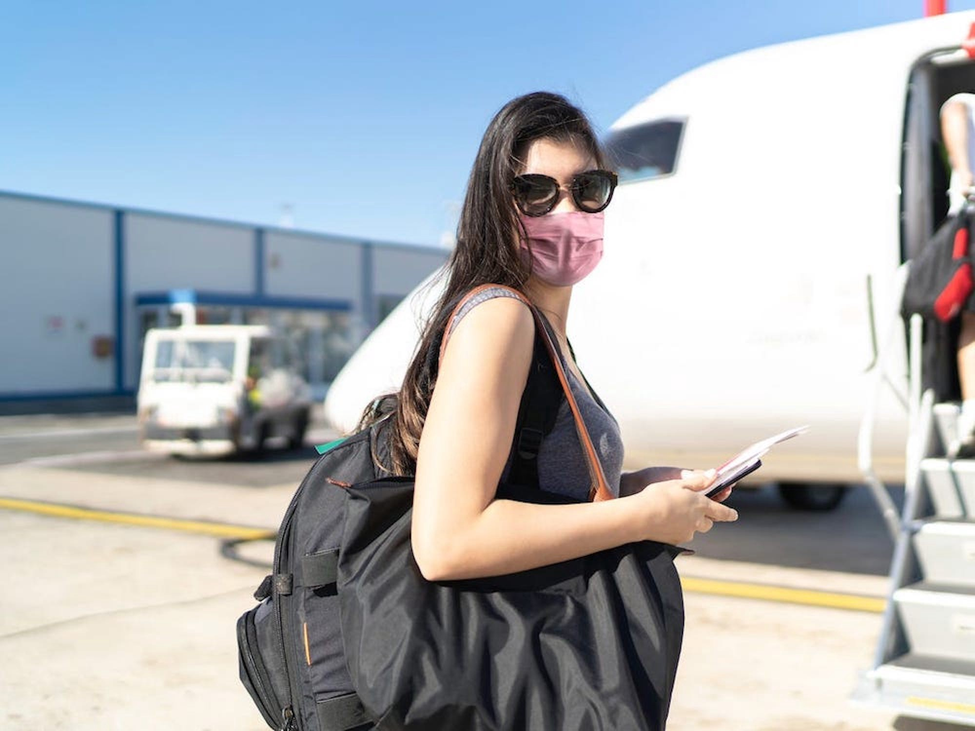 A masked traveler boards a plane.