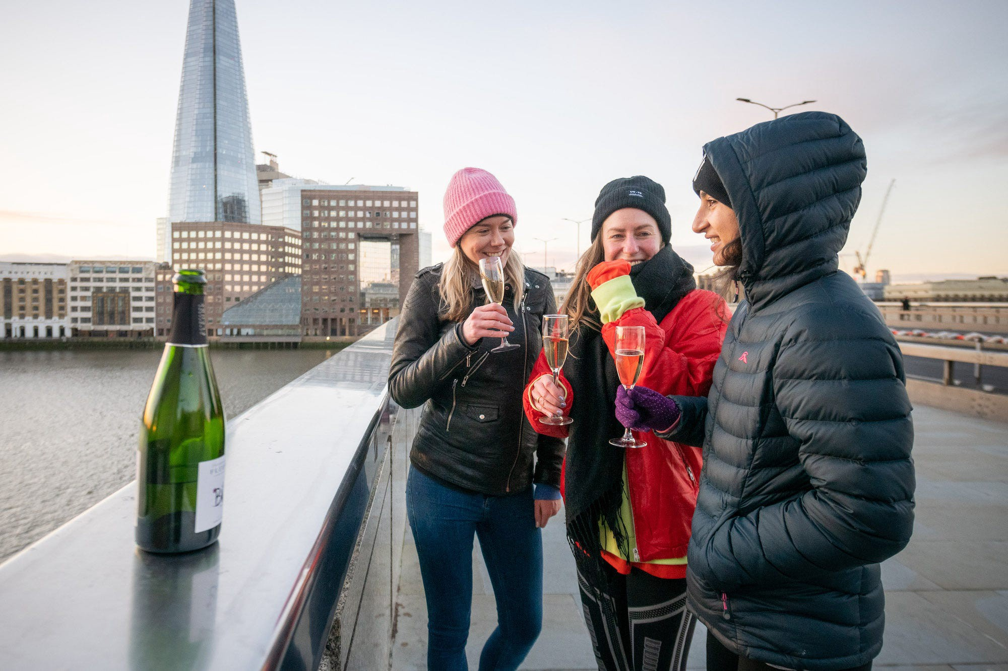 Friends enjoy a glass of Prosecco while watching the sunrise on London Bridge.