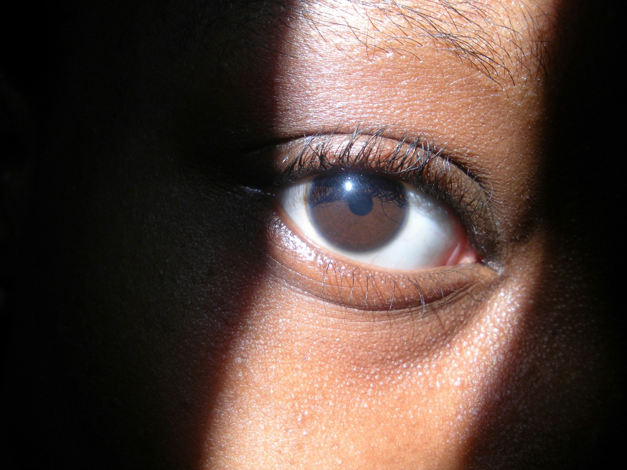 Closeup of a Black woman's eye, with light shining in a strip where her eyes is. Rest of face obscured by shadow.
