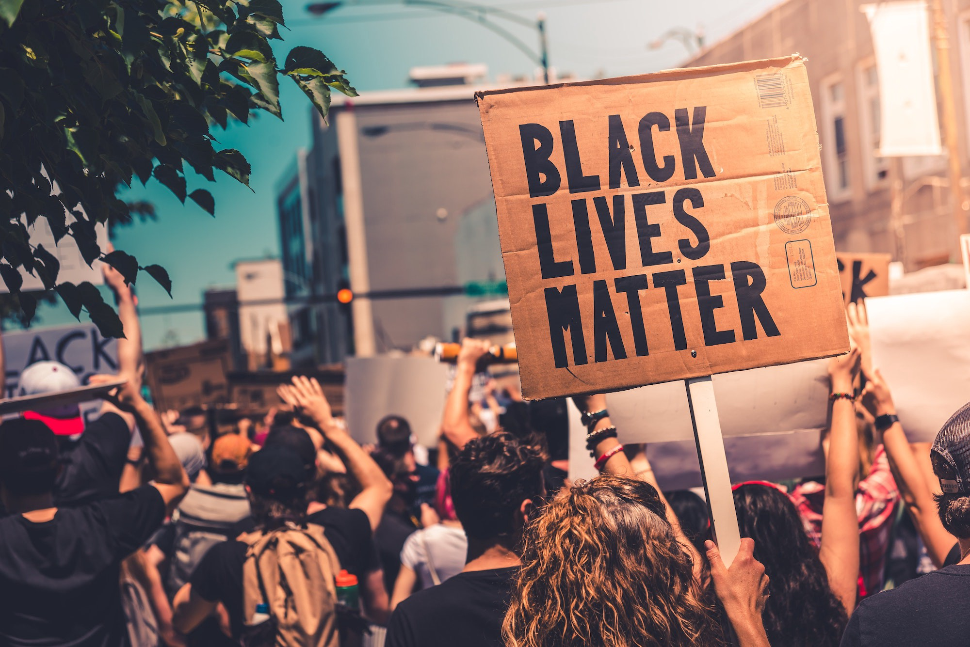 Protestors crowd a street, facing away from the camera. Facing the camera is a cardboard sign saying Black Lives Matter.