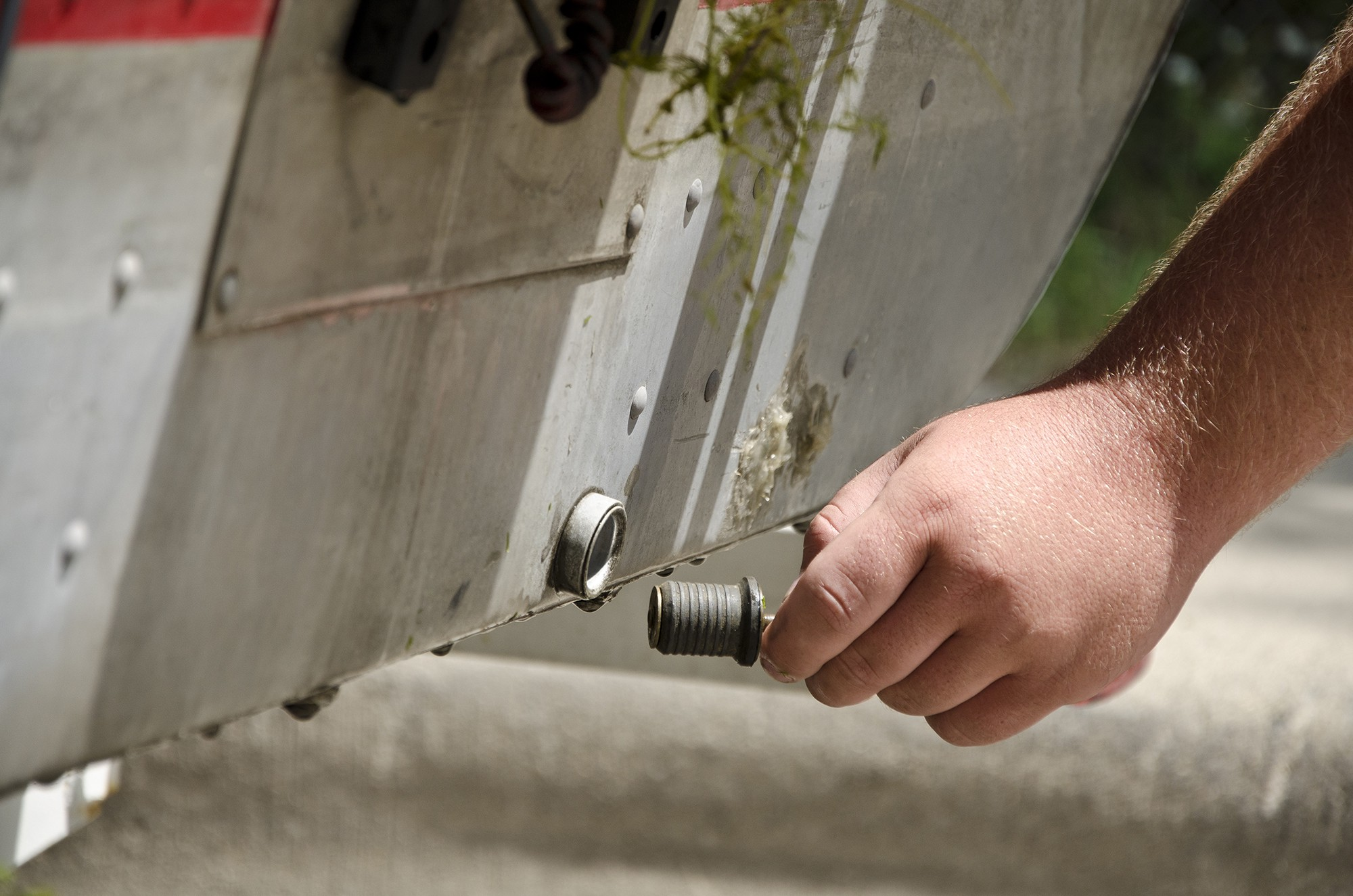 A hand holds the plug to a drain on the bottom of a boat.