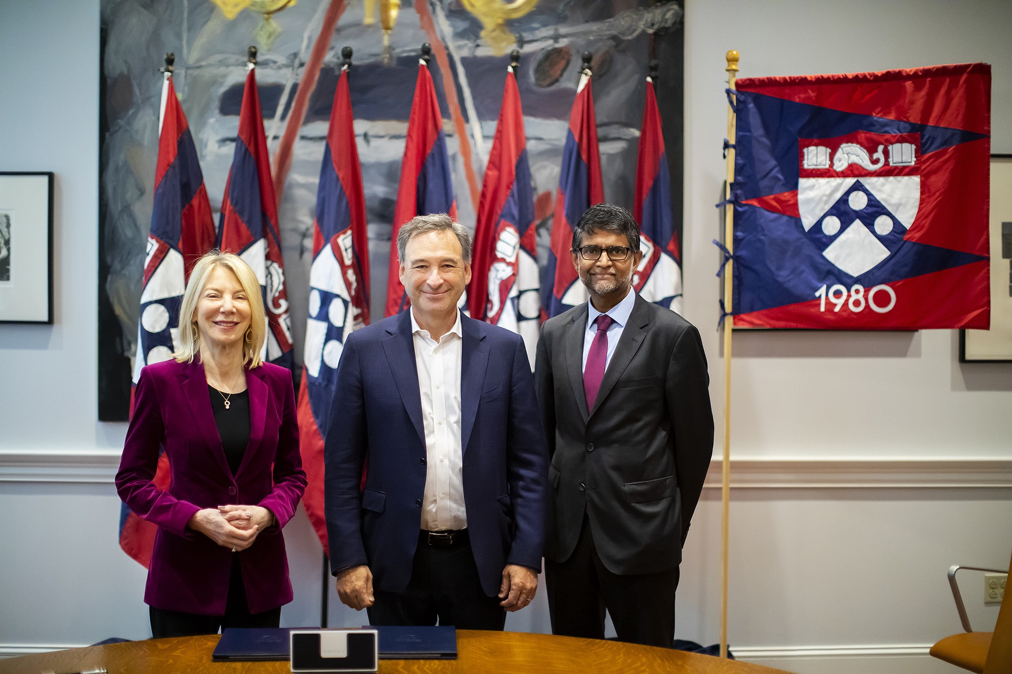 Amy Gutmann, Harlan Stone and Vijay Kumar stand in front of Penn flags and a class of 1980 banner.