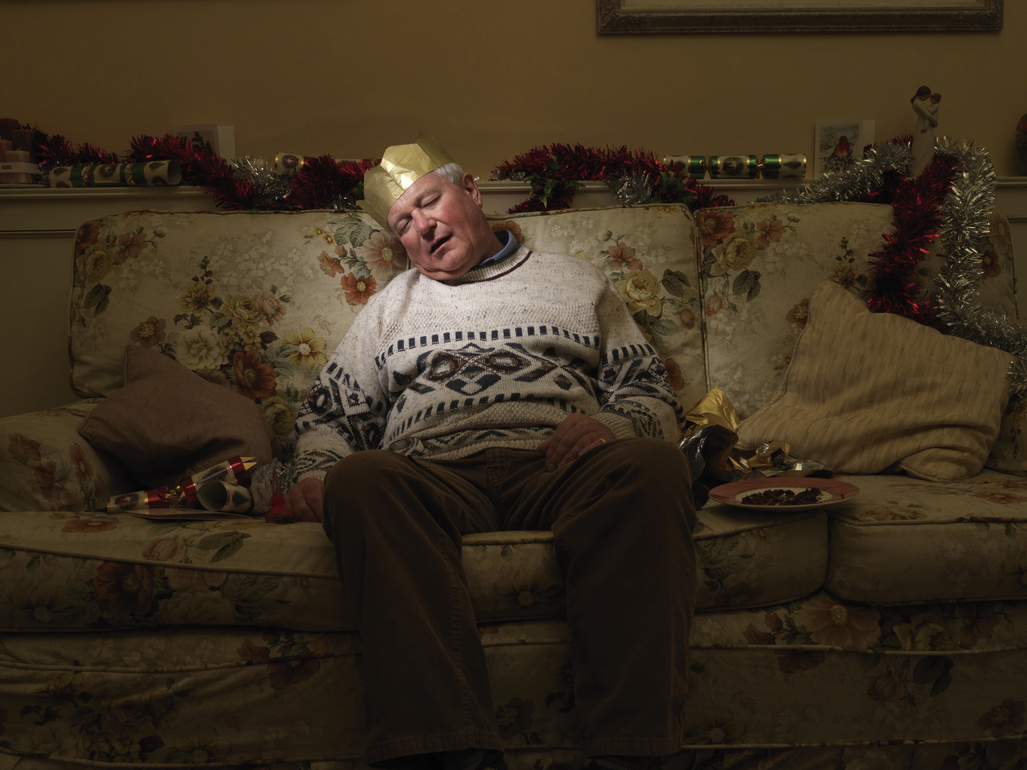 An old man with a gold paper crown hat sleeping on the couch.