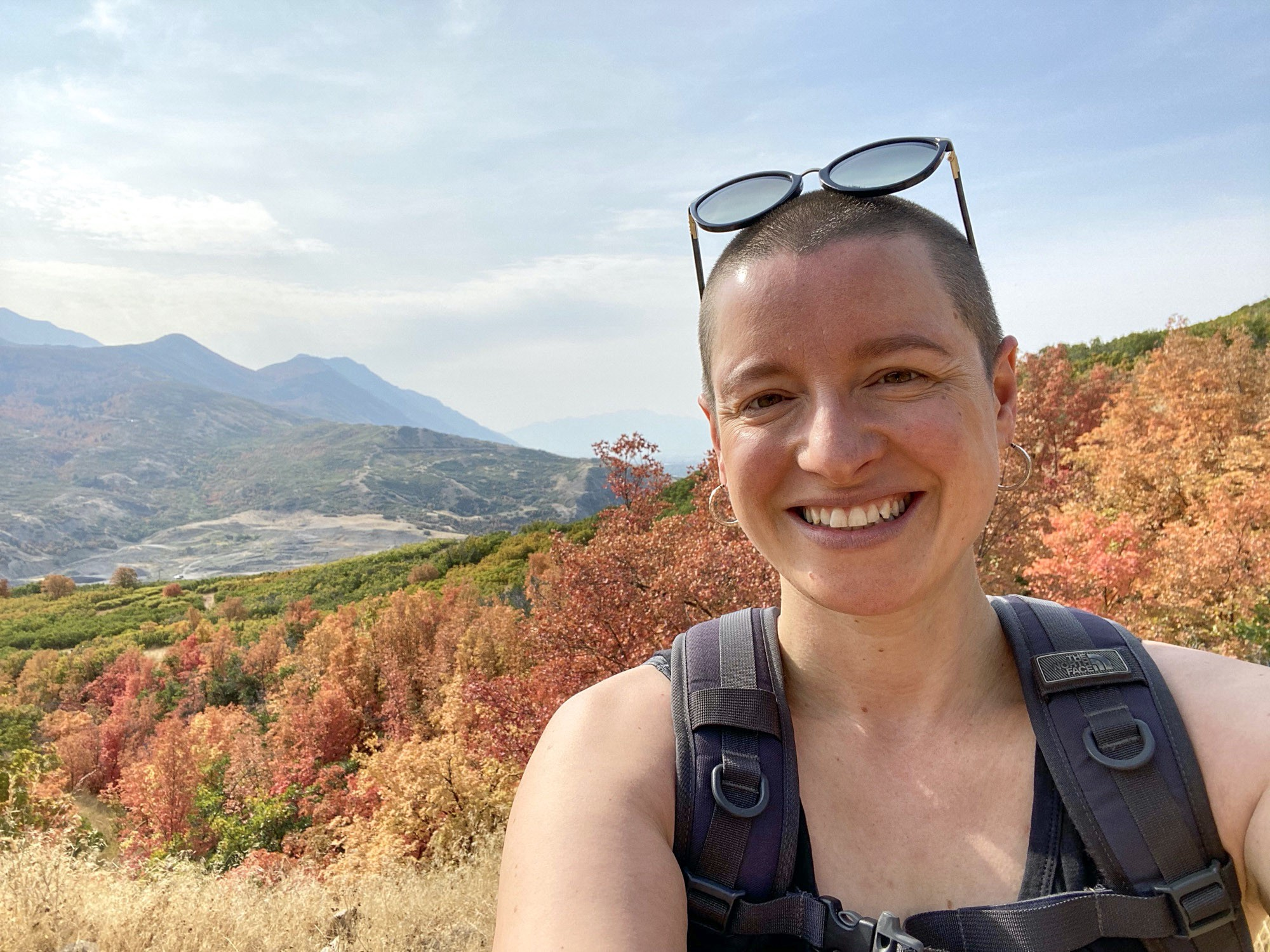 Sarah Dopp is standing on the top of a hill on a hike with autumn leaves in the background. She is smiling.