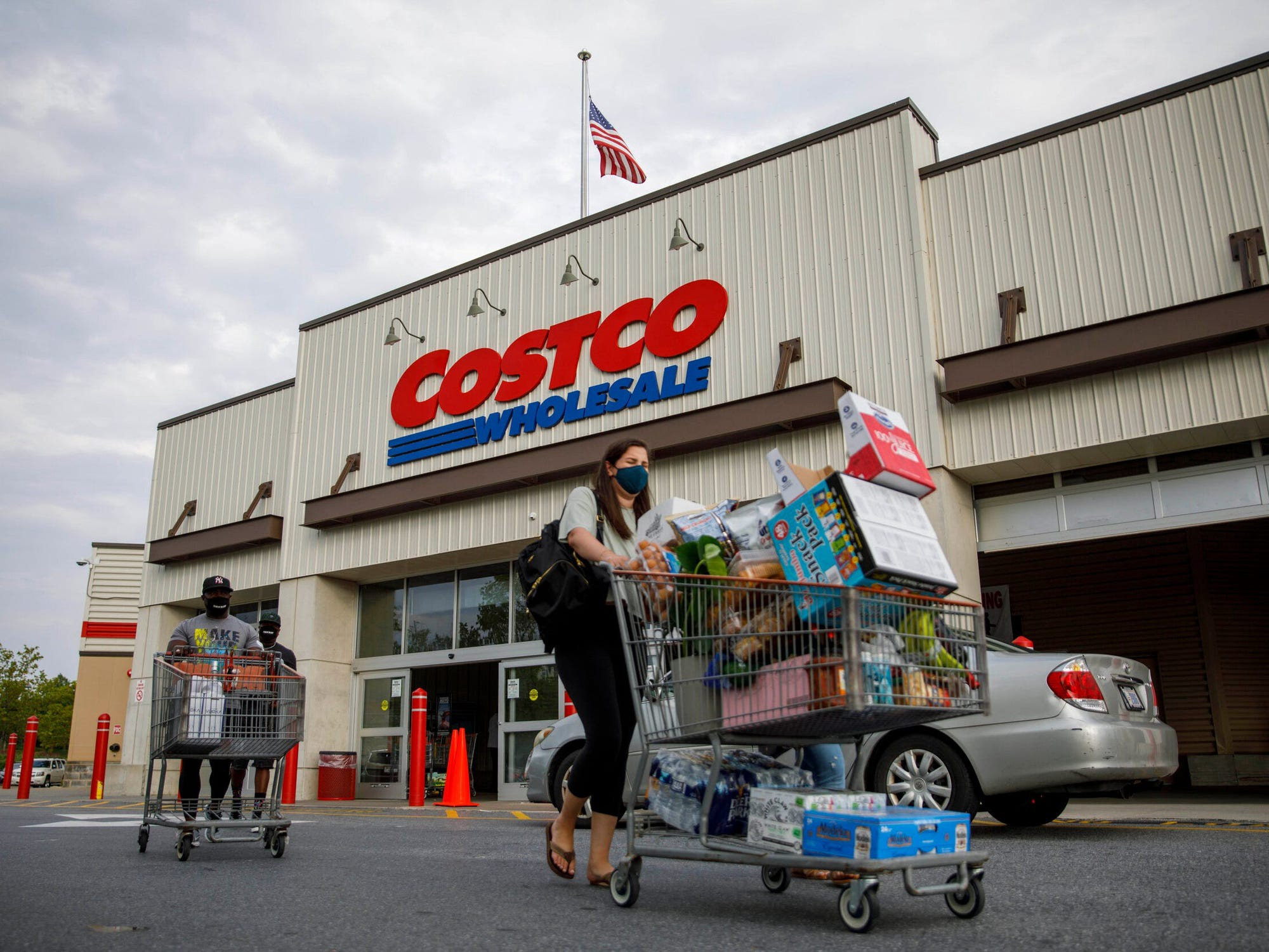 A masked customer pushing a shopping cart in front of a Costco.
