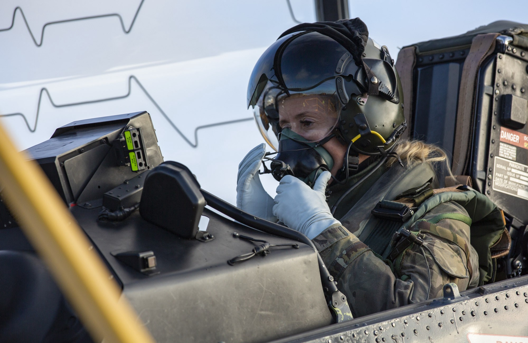 A woman in a flight suit and helmet sits in an RAF aircraft