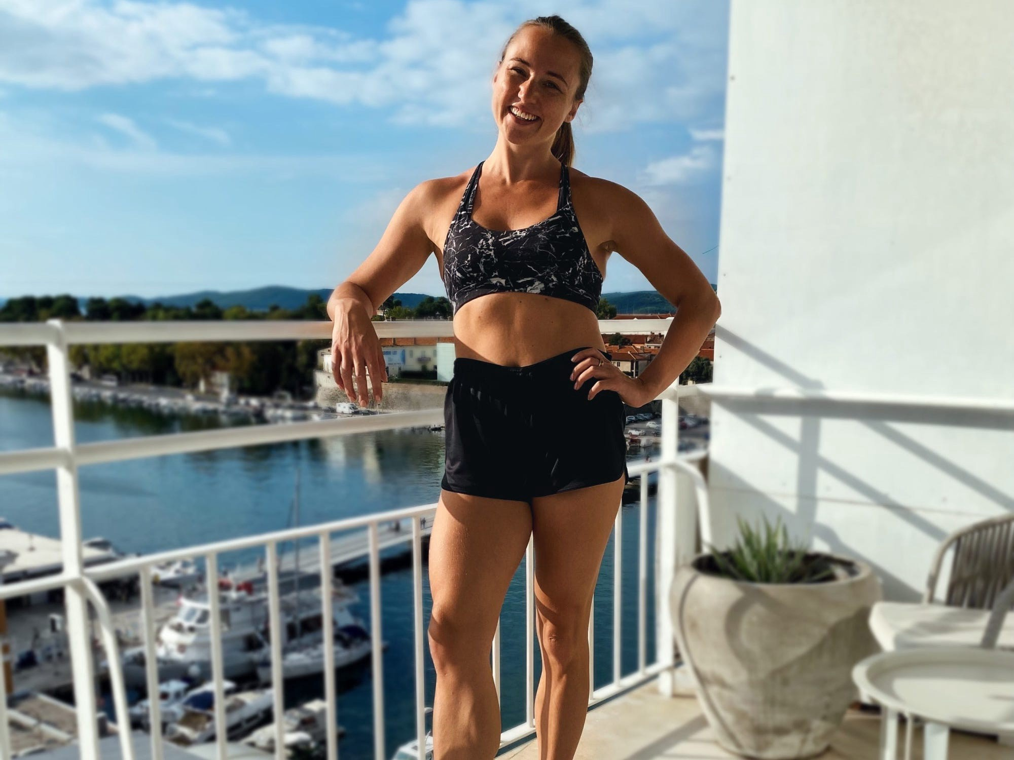 The author, Rachel Hosie, on a balcony overlooking a body of water while on vacation.