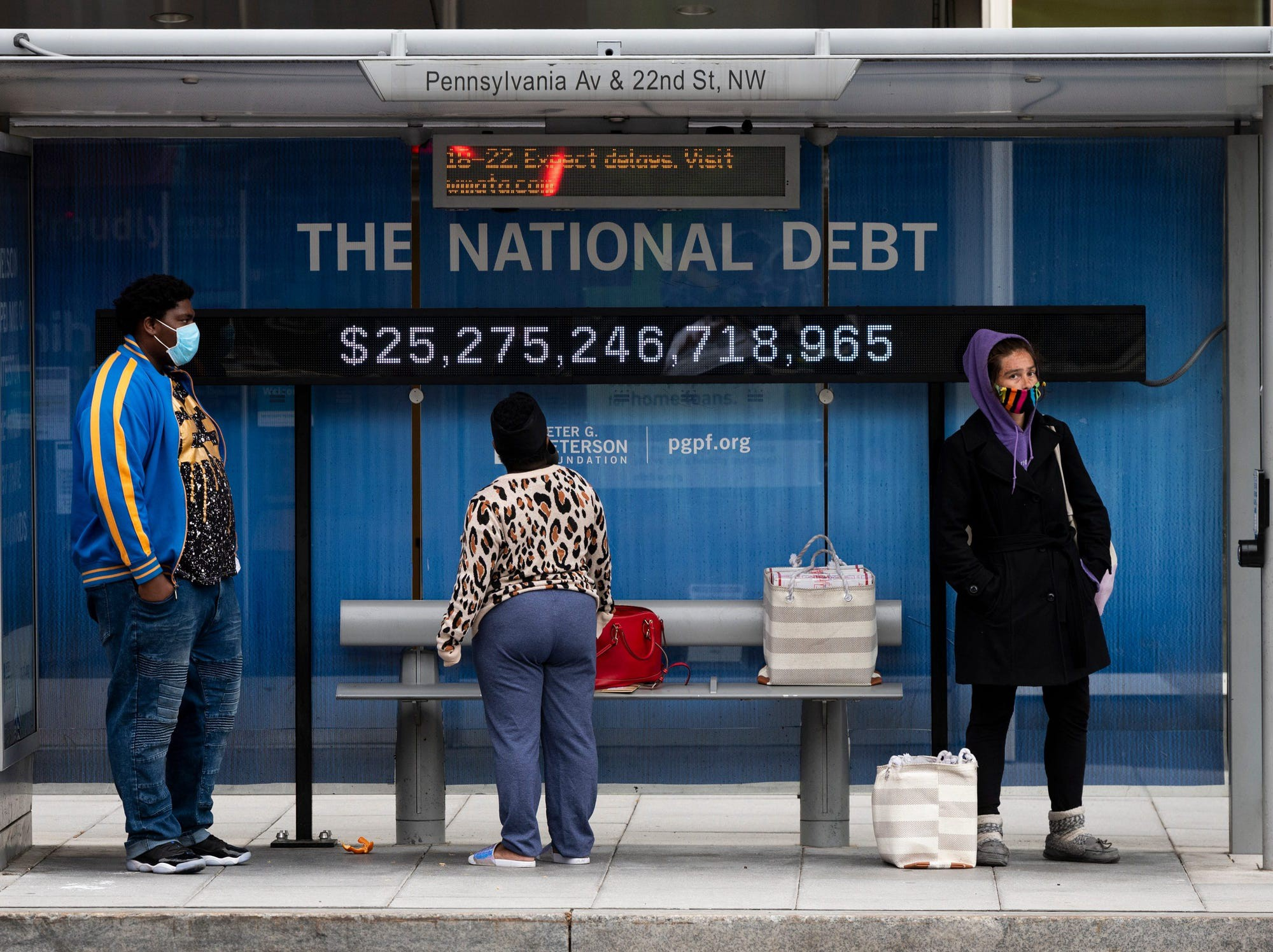 Passengers wearing face masks wait for their bus in front of a national debt display on Pennsylvania Ave. NW in Washington on Monday, May 18, 2020.