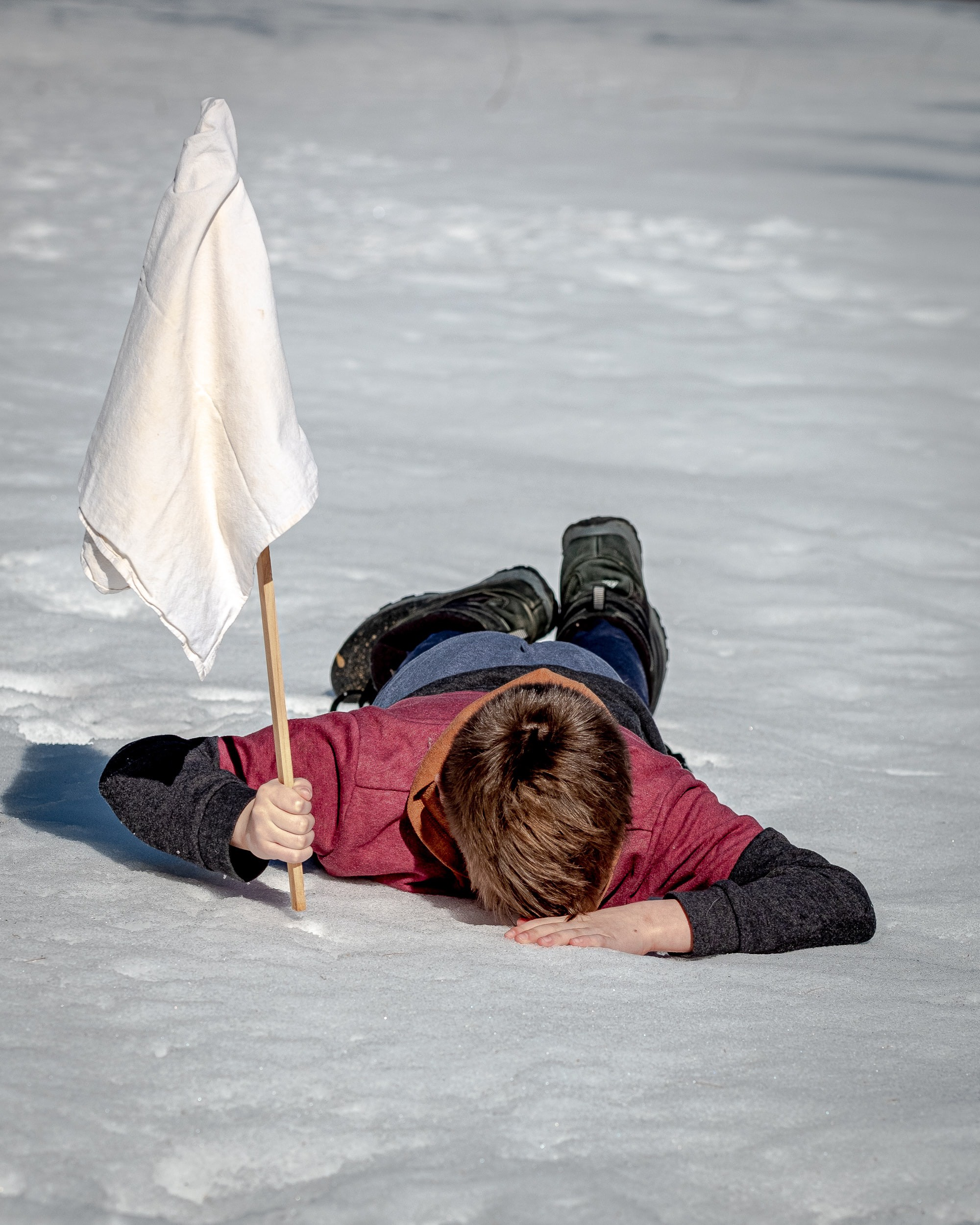 Person lying prone on ice with a white flag in their hand