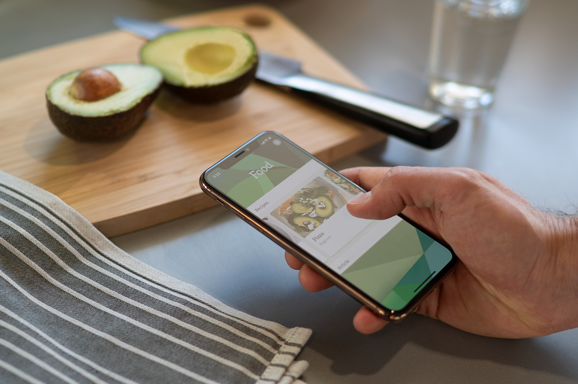 An individual using an app on their phone with a cutting board and an avocado in the background.