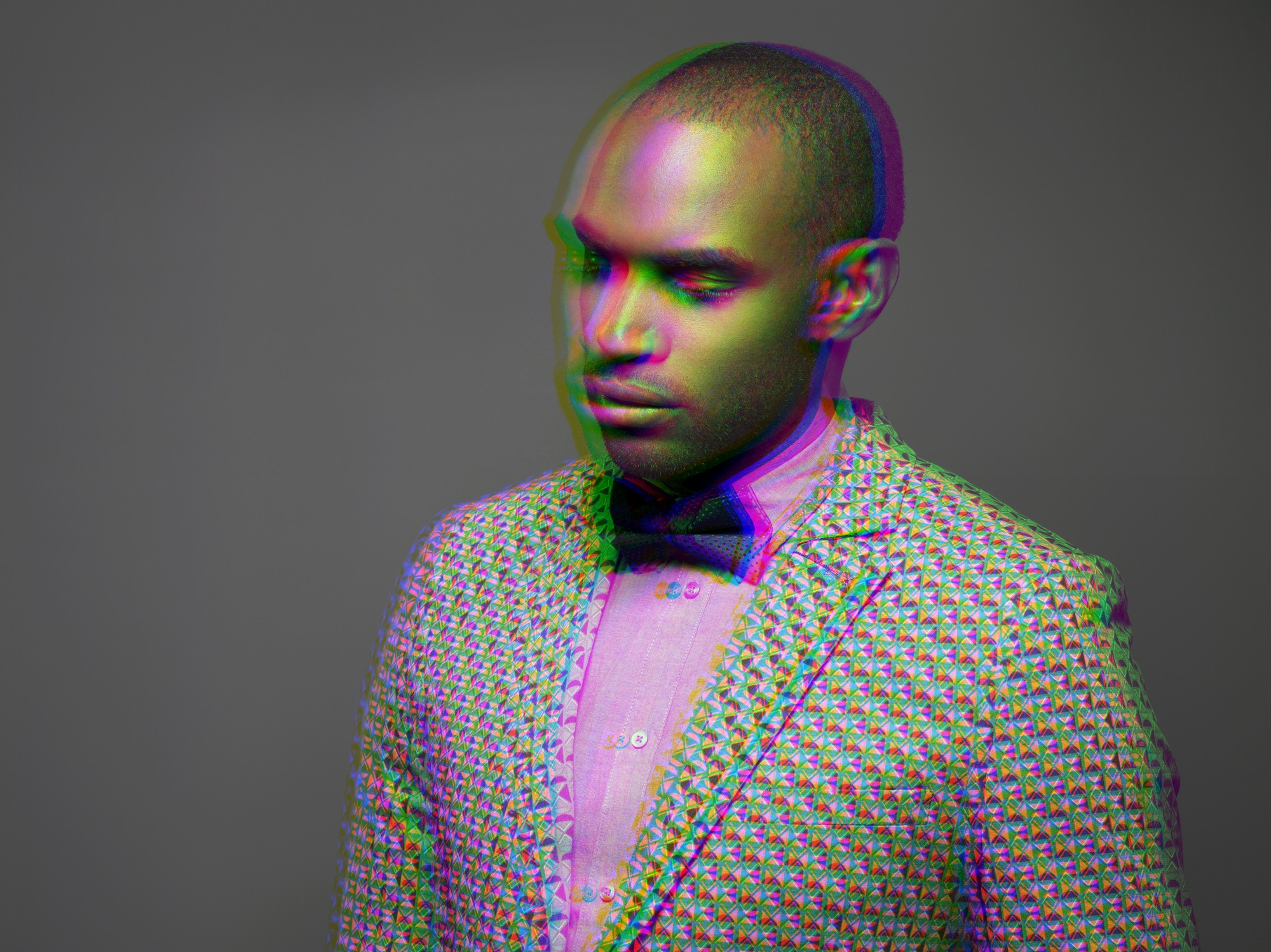 Multiple exposure shot of a Black man wearing a suit looking down.