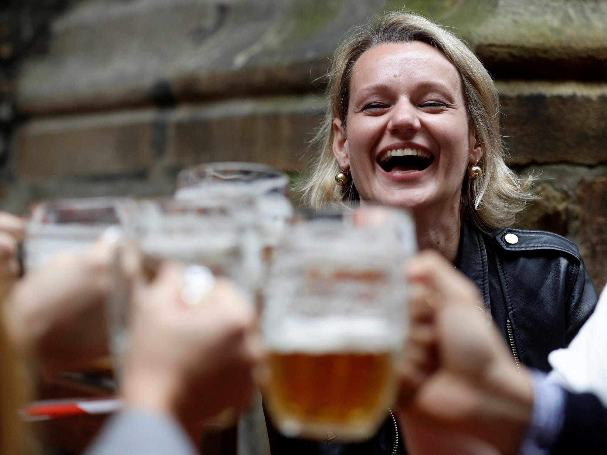 An individual laughing and holding up a beer.