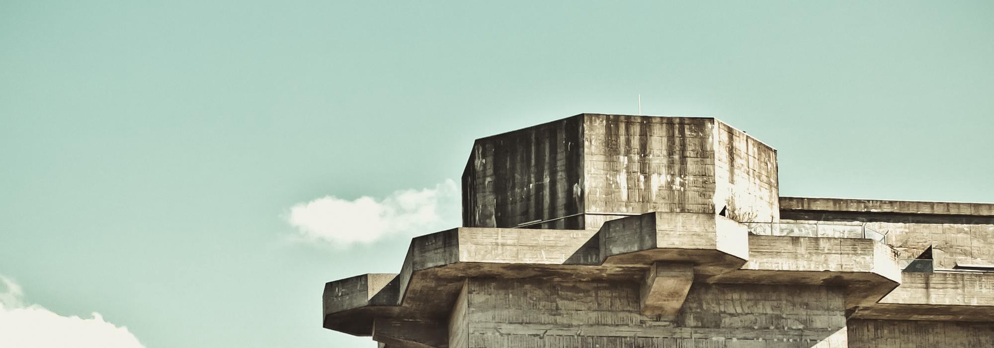An old, desolate concrete fortress stands against a clear blue sky.