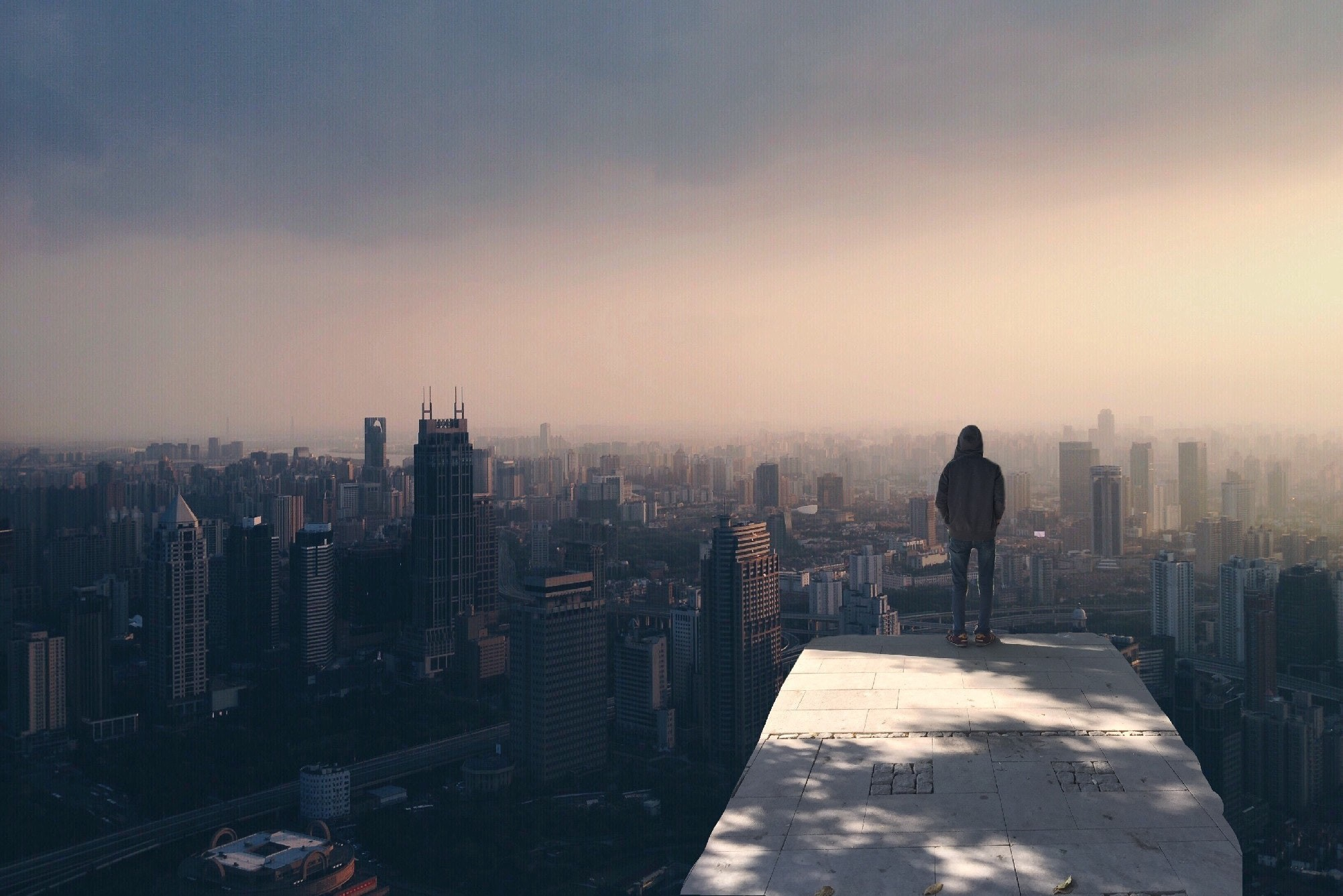 Person standing on top of a building in the city