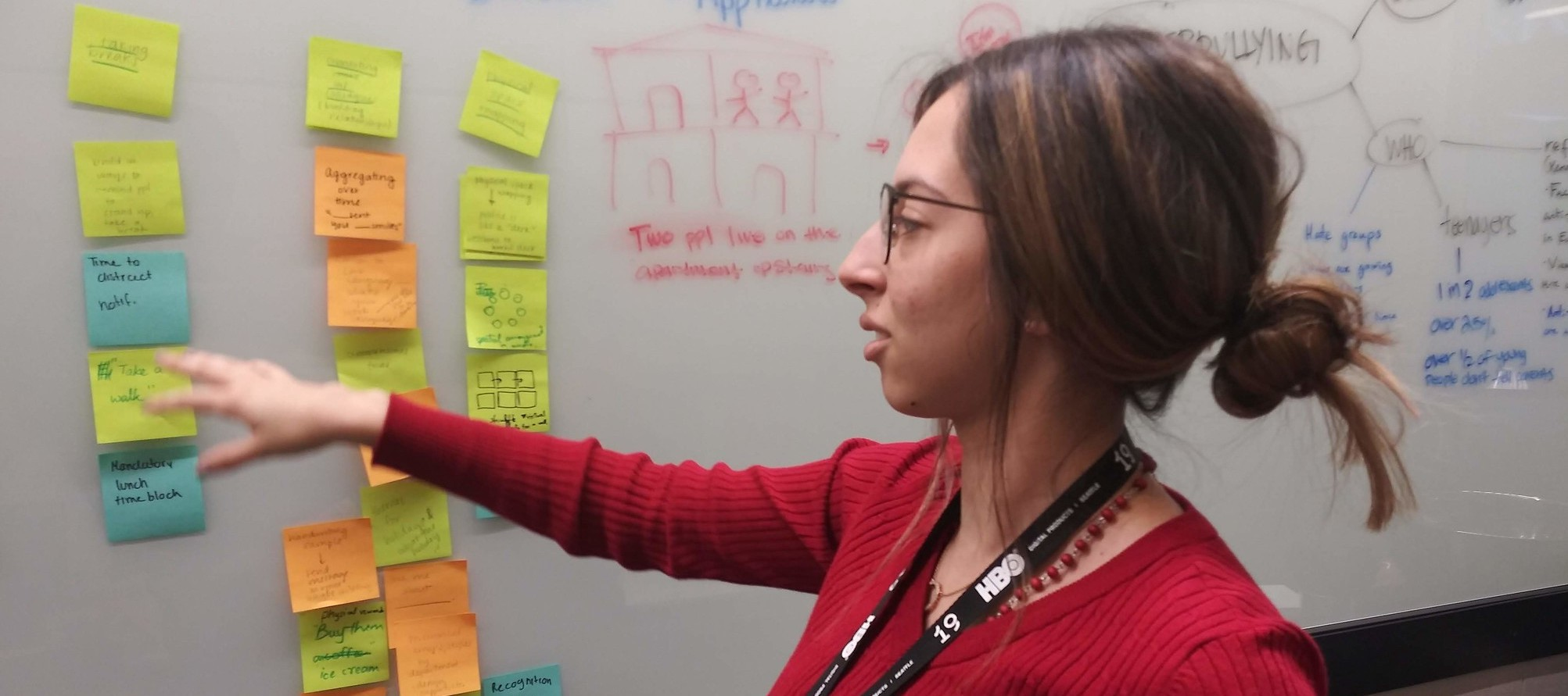 Woman with glasses in a red sweater pointing at Post-its on a whiteboard