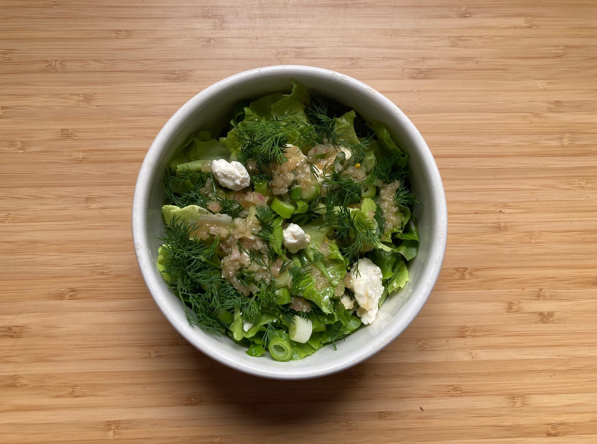 A very green salad with scallion, feta cheese, and dill is topped with sherry vinaigrette.