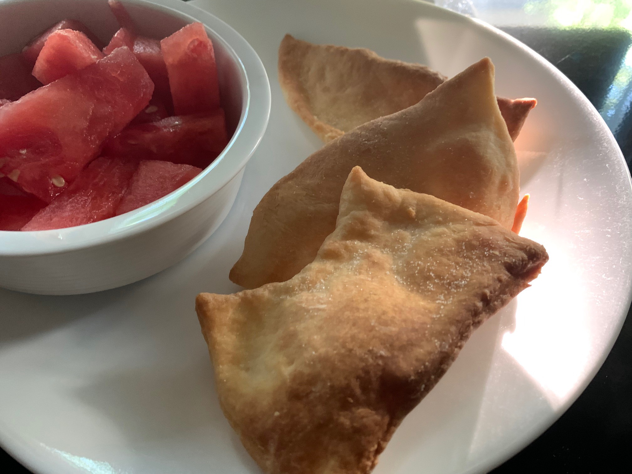 A small dish of sliced watermelon accompanies three glorious Rollkuchen. The perfect pairing of flavour and texture.