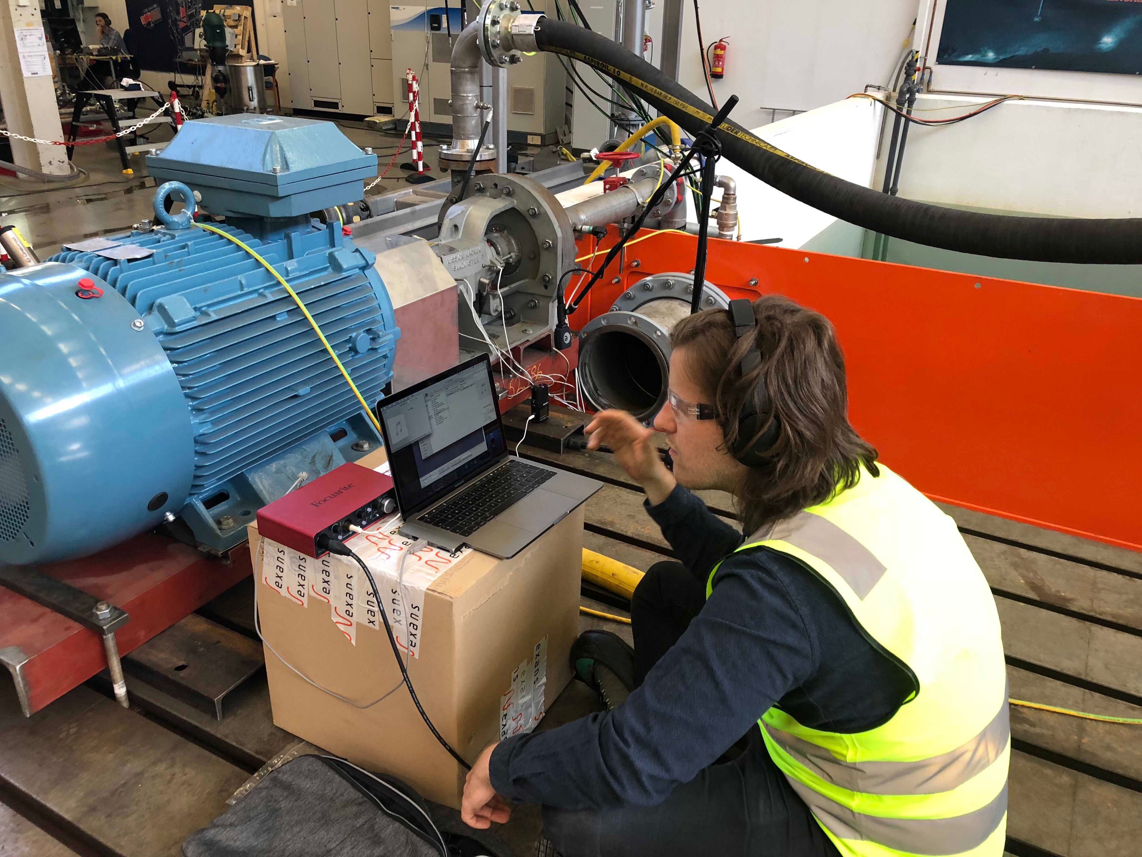 Man sitting in front of his microphone equipped laptop, in front of a large pump, doing experimental analysis of audio data