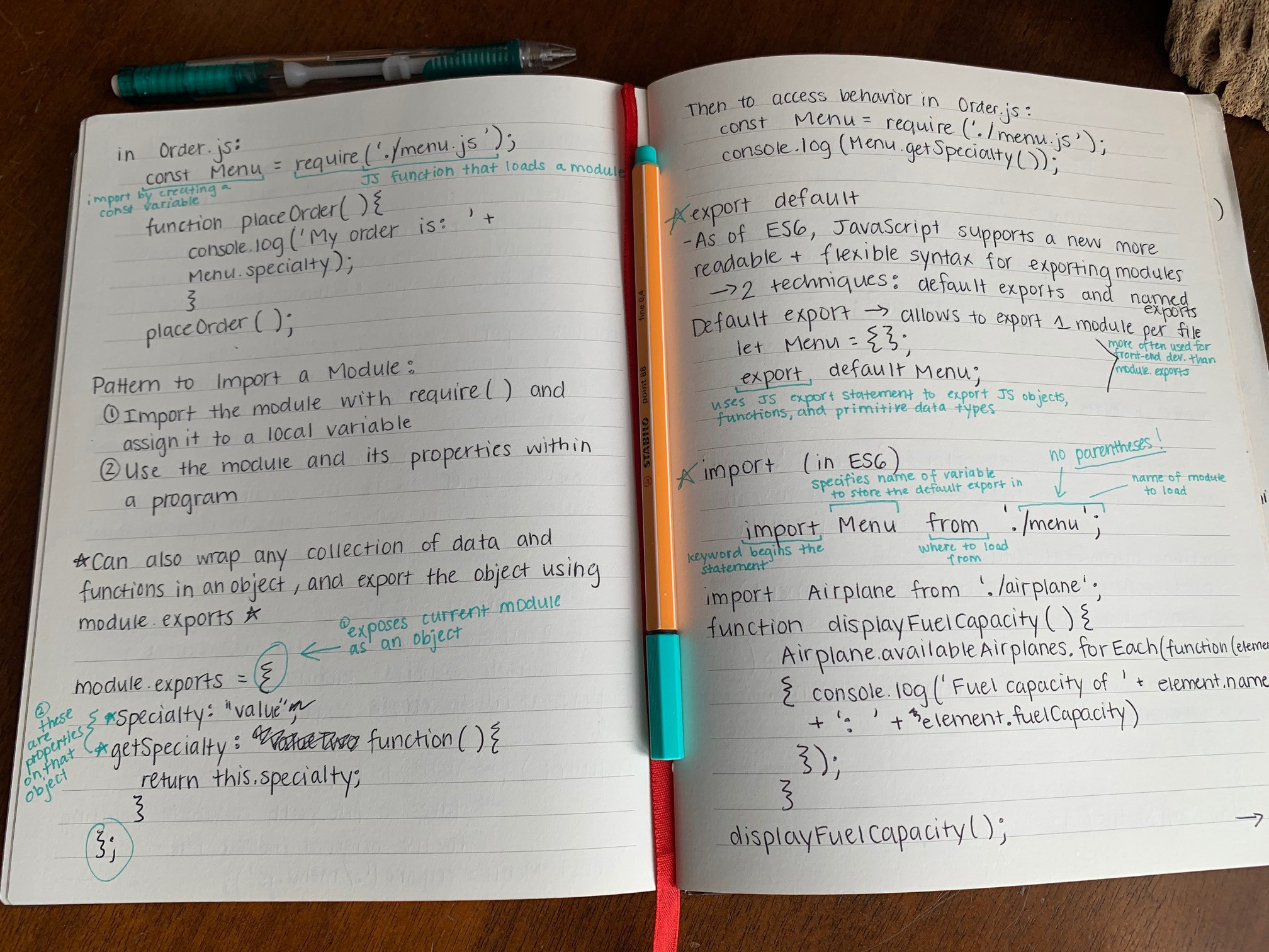 An open notebook with handwritten notes on using modules in JS, with a pen lying between pages