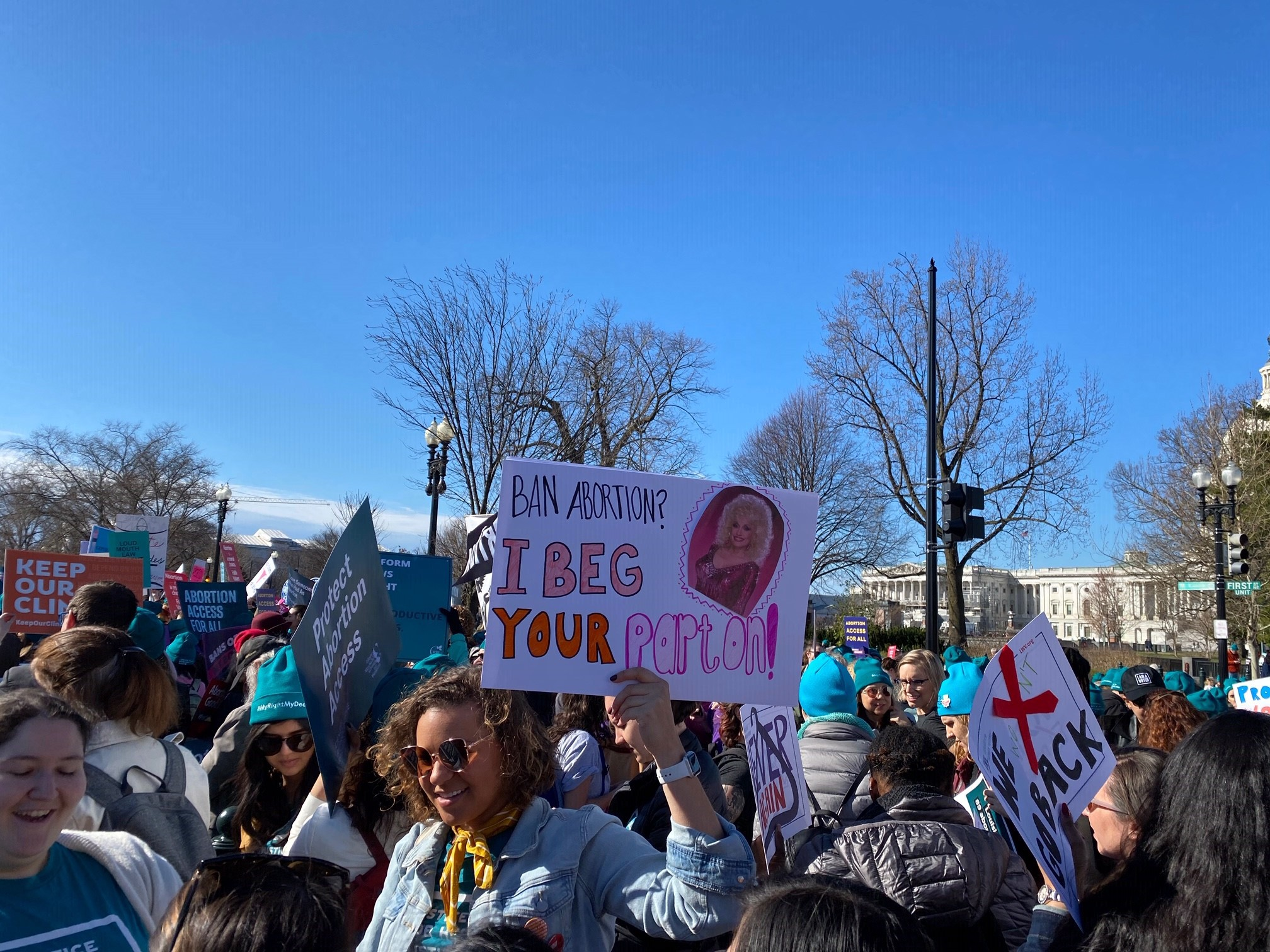 """Woman holds a pro-choice signs that reads, """"Ban abortion? I beg your Parton!"""" with a photo of Dolly Parton on the sign."""