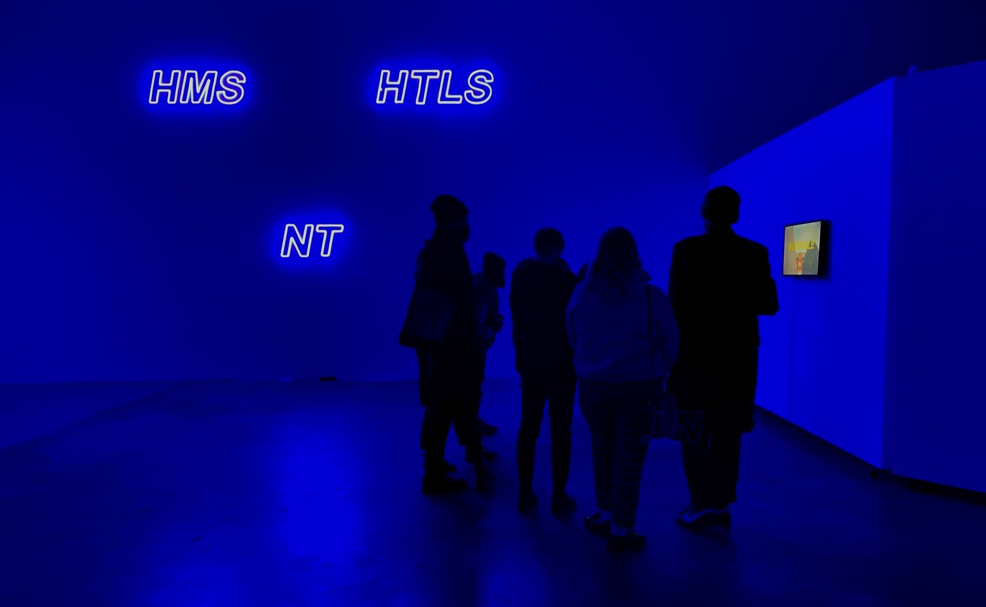 Museum visitors standing in front of a blue neon light installation in the Plaxall Gallery in Long Island City, New York.