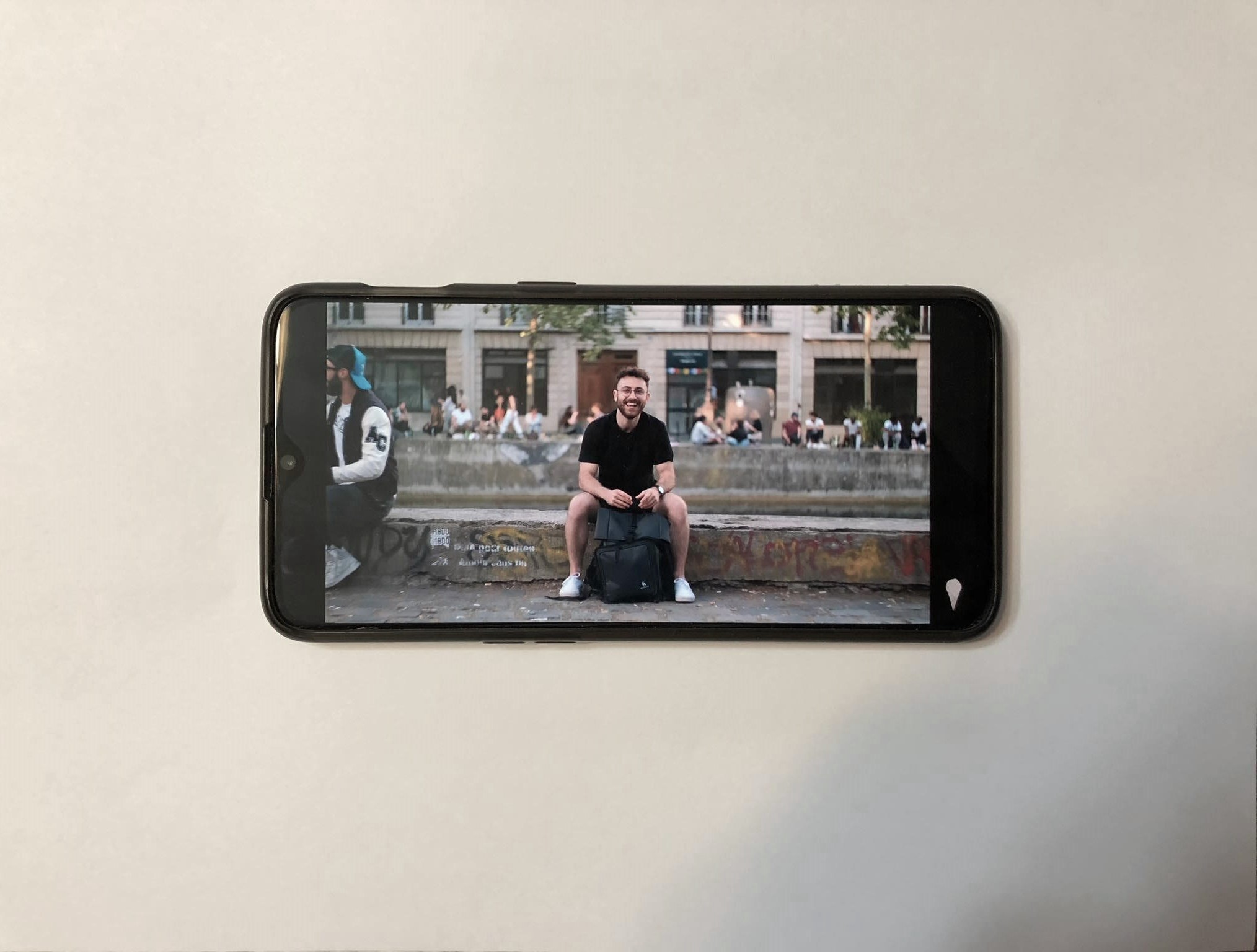 A OnePlus 6T laying flat on a white background playing a YouTube video by Nathaniel Drew