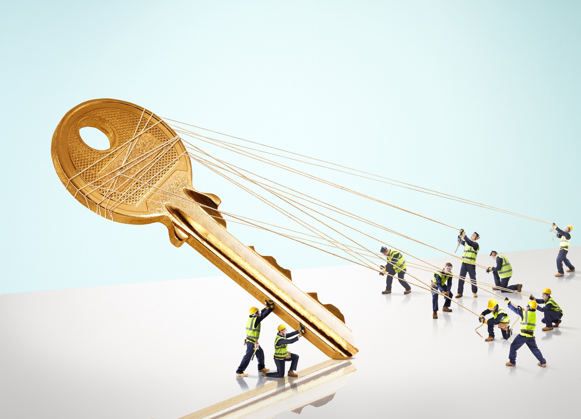 A group of miniature builders trying to erect and pull a giant gold key.