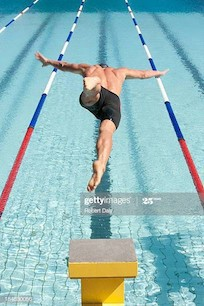 Swimmer leaping off starting block into the pool. He has a clear lane in which to swim.