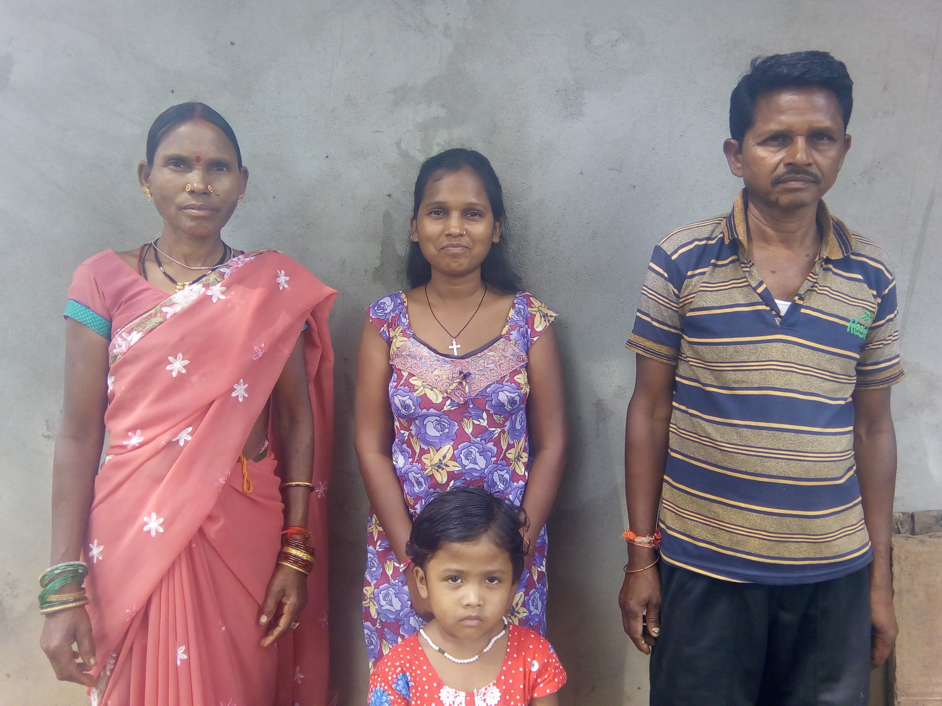 A family of 4 individuals starting with the wife, daughter and father from left to right and a younger daughter in from.