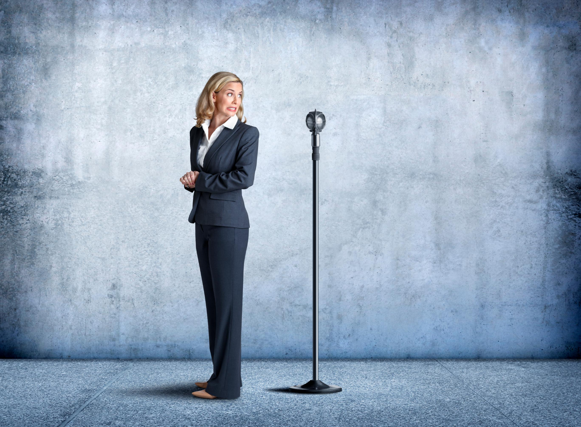 A businesswoman sheepishly turns her back to a microphone as she is exhibits fear of public speaking.