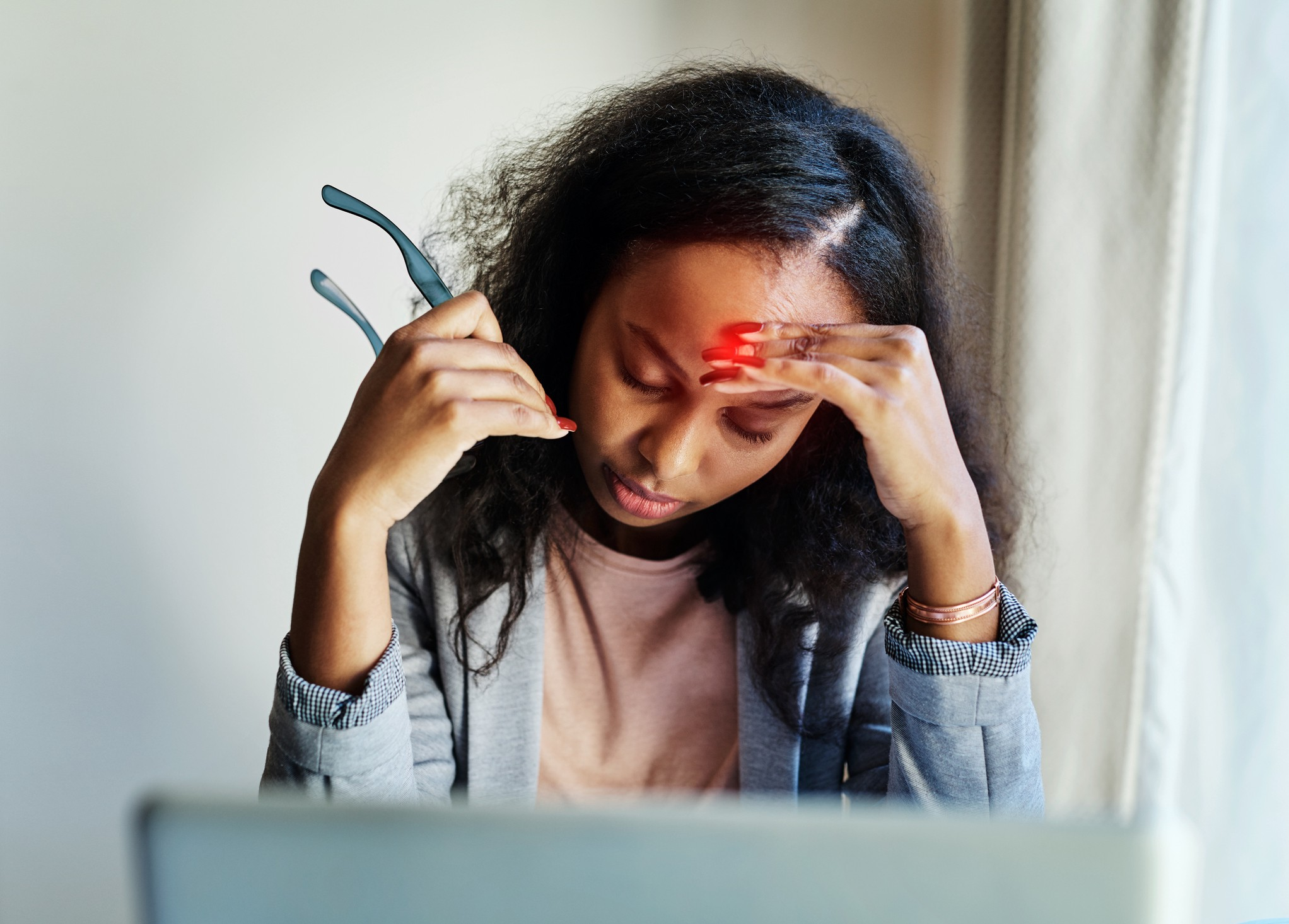 Shot of a young woman suffering from a headache while using a laptop at home.