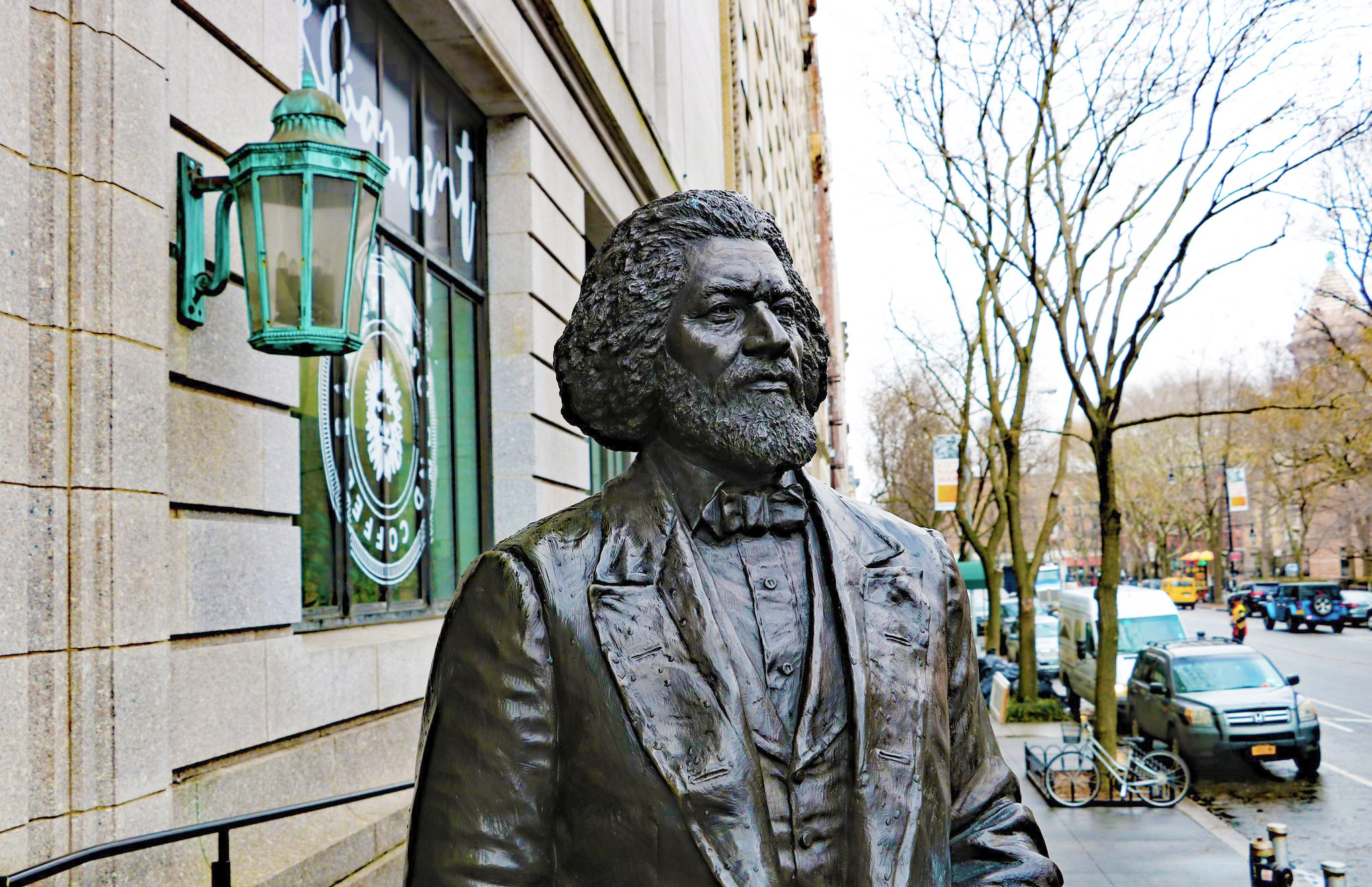 Bronze statue of a man from the nineteenth century. He's looking forward, and stands next to a decorative copper lamp.