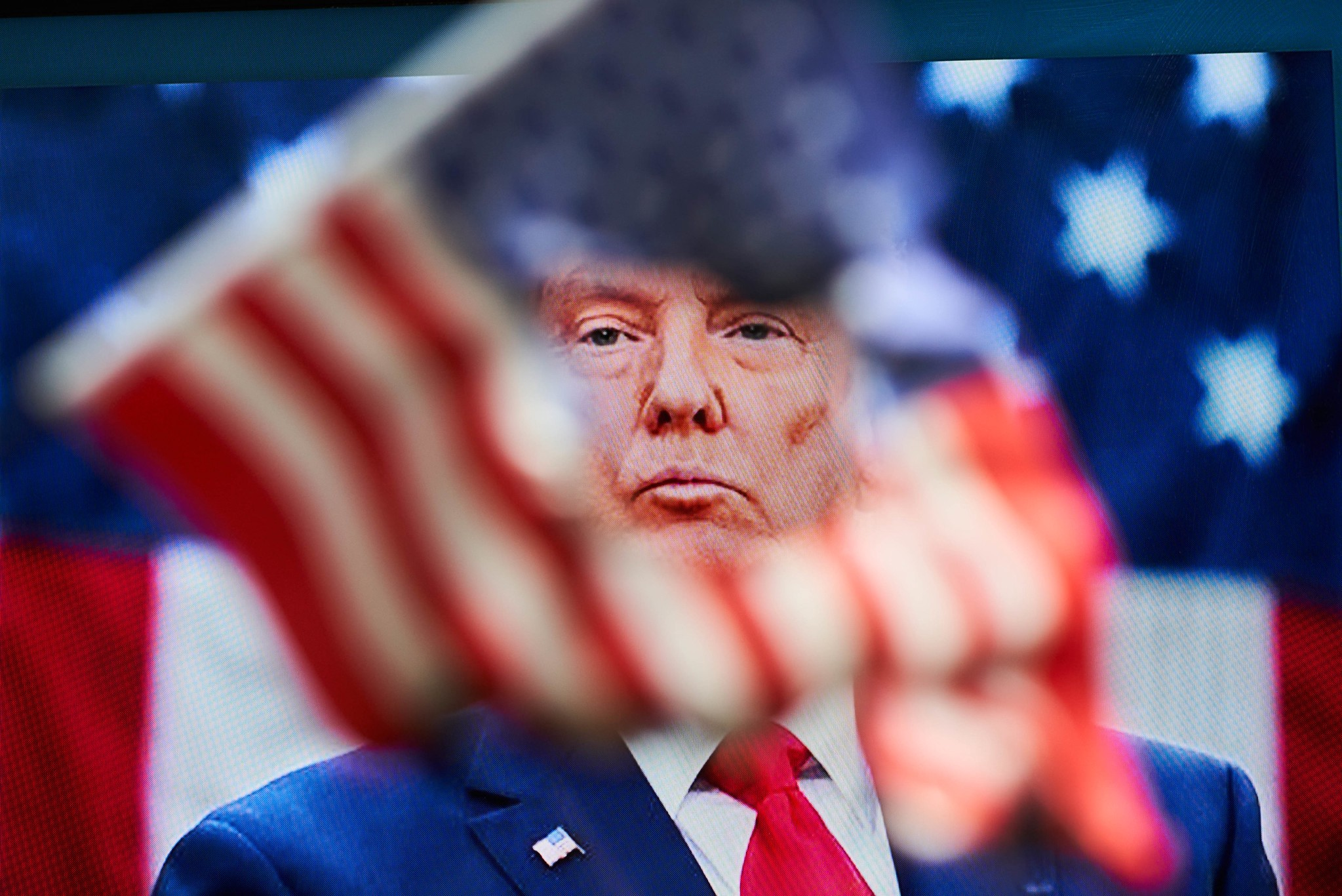 Donald Trump's face as seen through a half-burnt American flag with a hole, against a flag backdrop