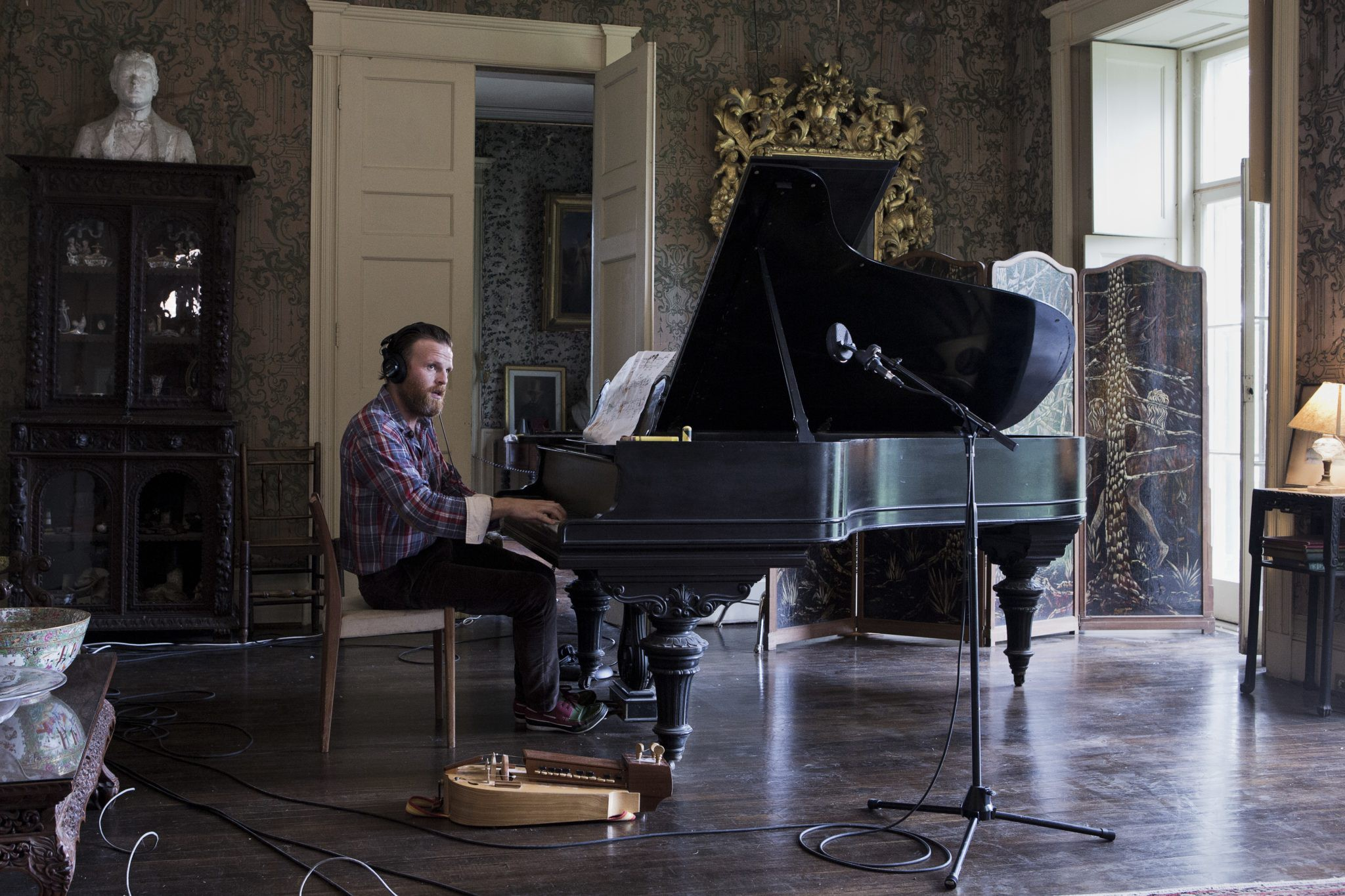 A man plays the piano in a grandiose room with an ornate mirror and a bust nearby.