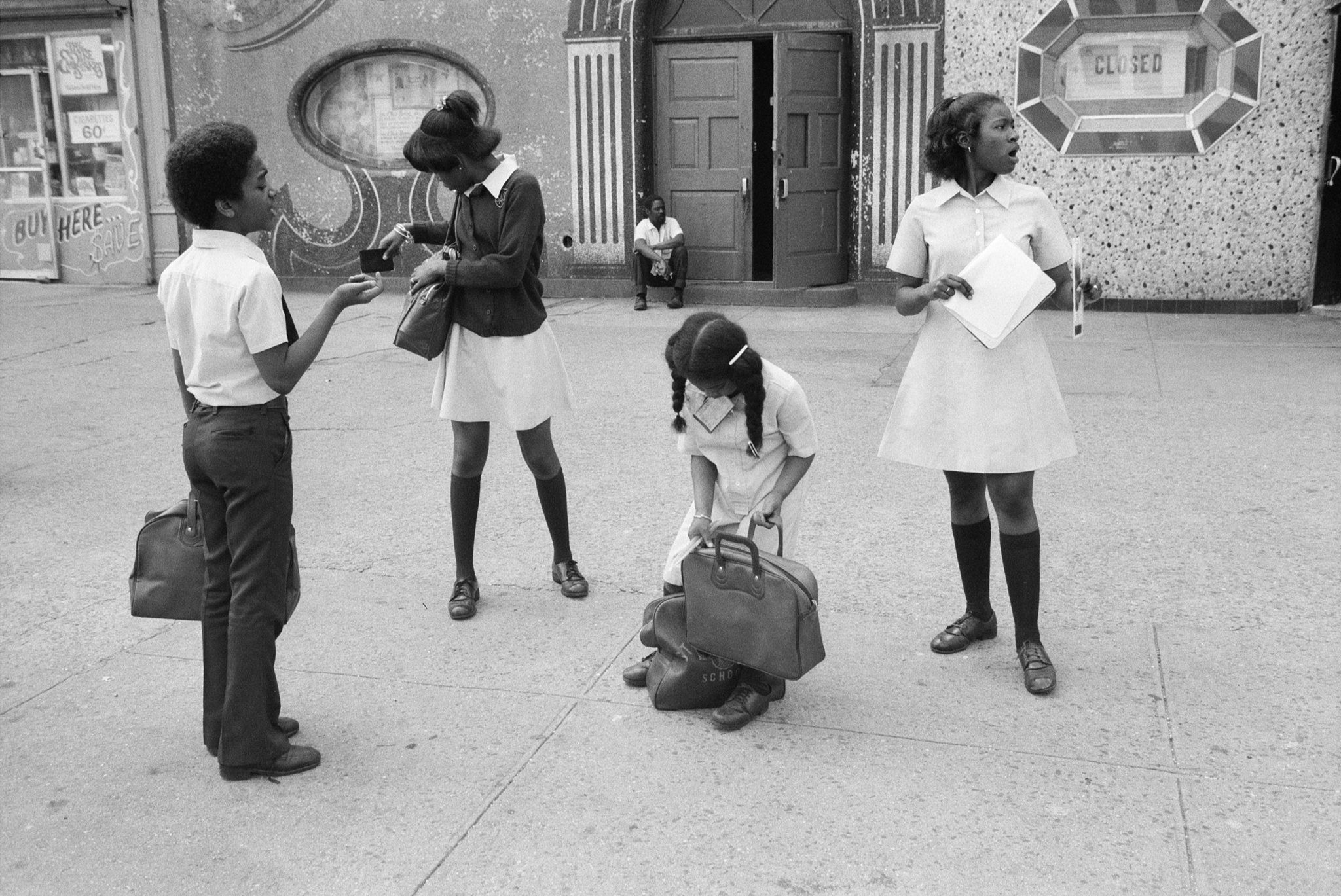 Black and white photograph of four children getting ready to head to school.