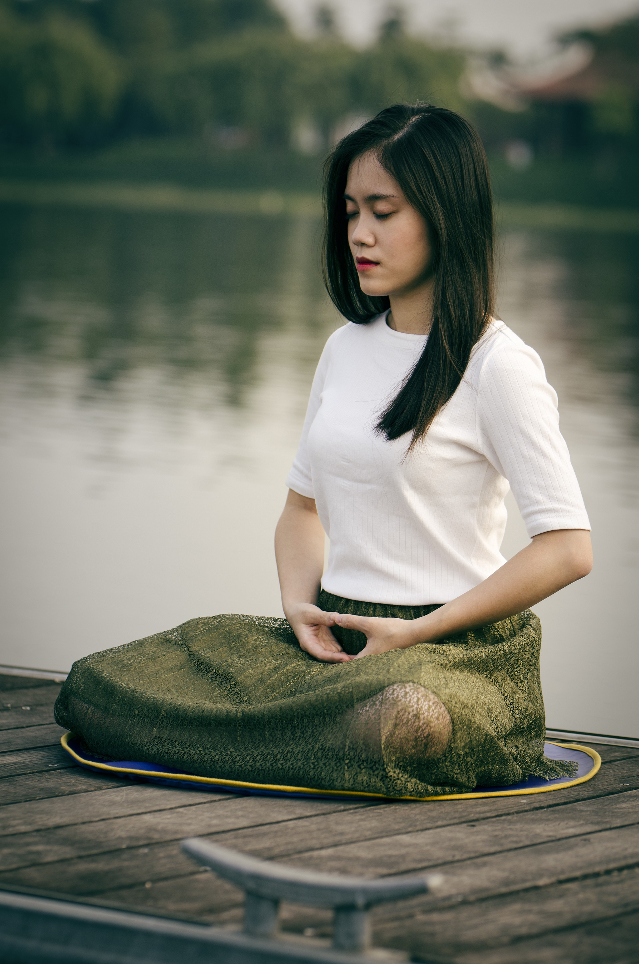 Woman breathes in meditation by river