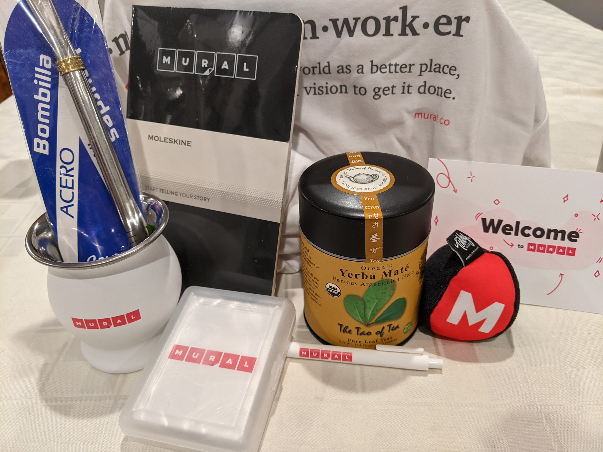 Photo of an assortment of MURAL branded swag, including the materials needed to make yerba mate tea.