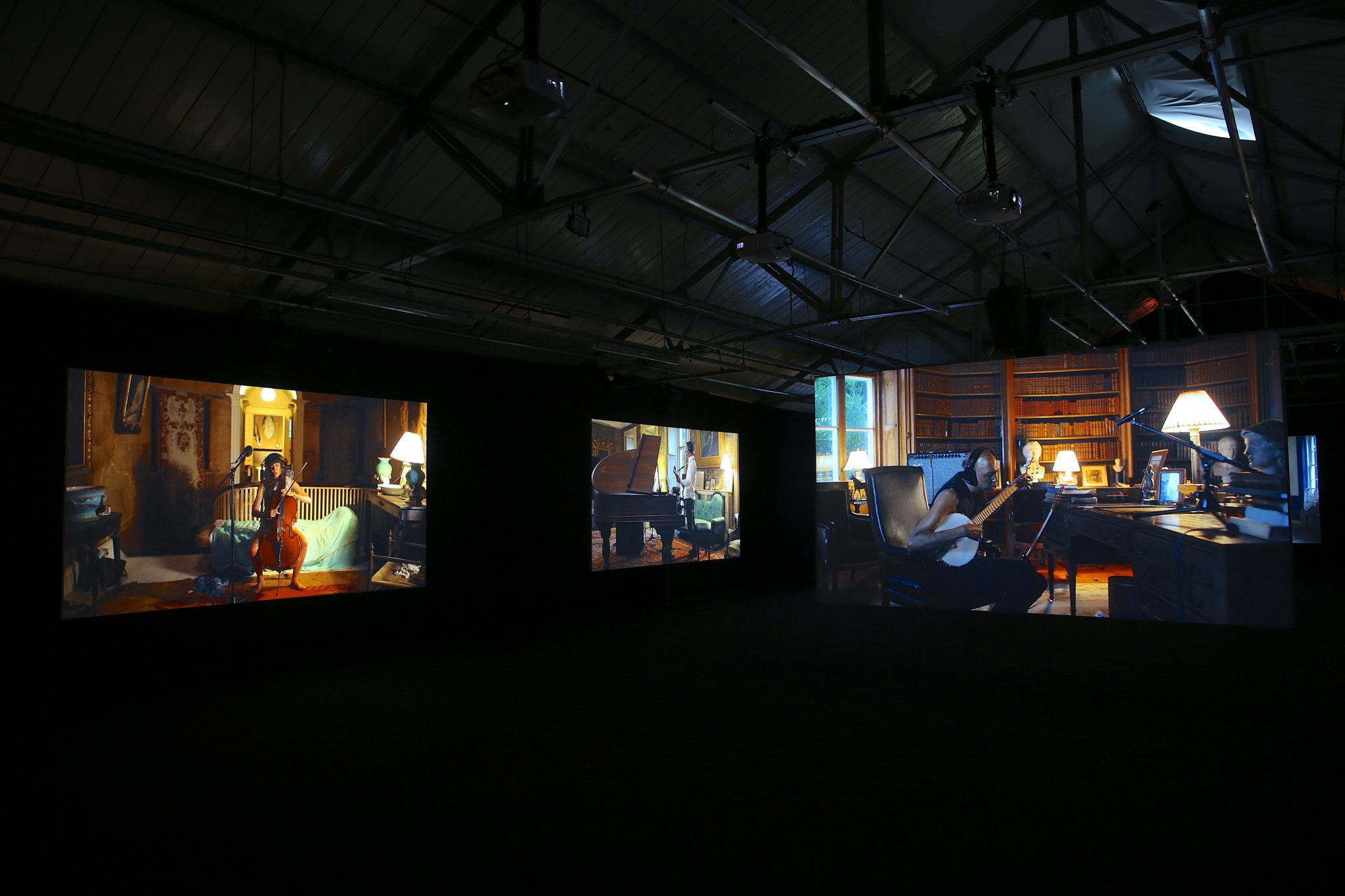 Blacked out room hosting several large projector screens showing musicians playing alone in separate rooms.