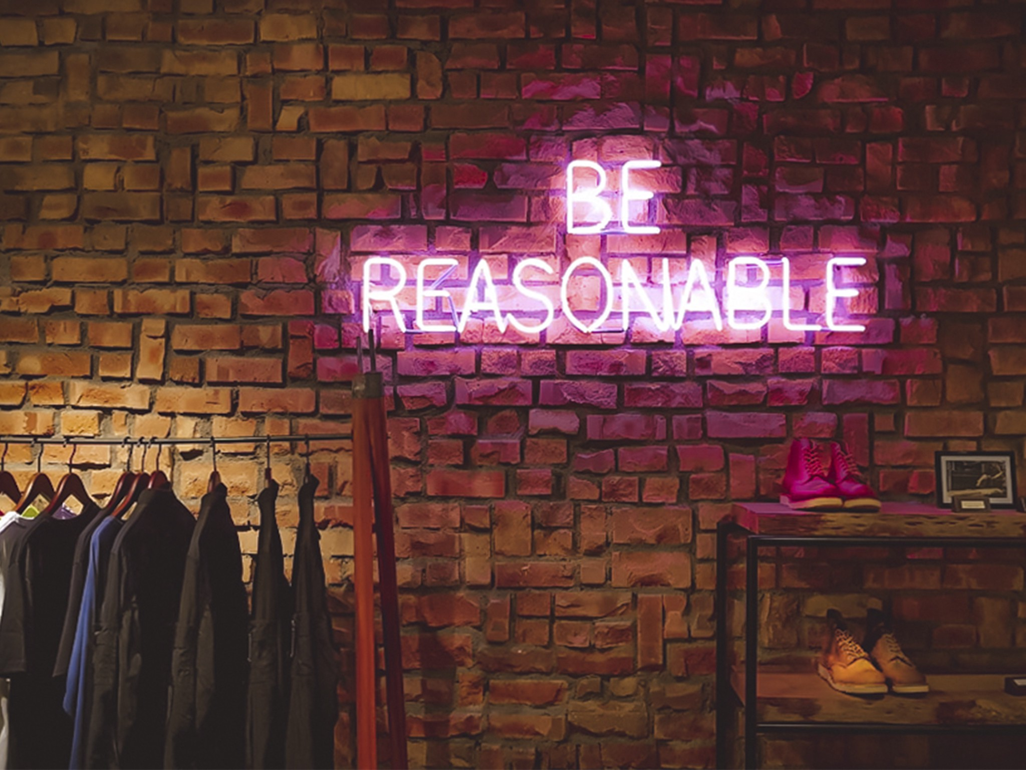 Be reasonable neon sign against brick wall expressing fashion and sustainable buying habits