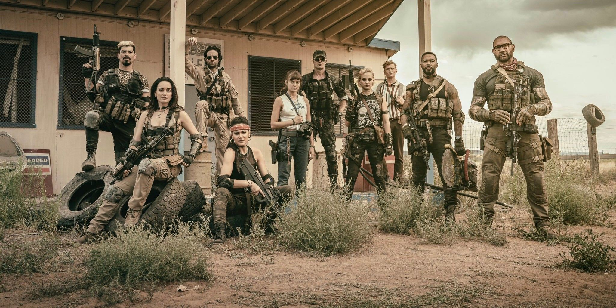 A bunch of armed mercenaries posing in front an abandoned house i the desert.