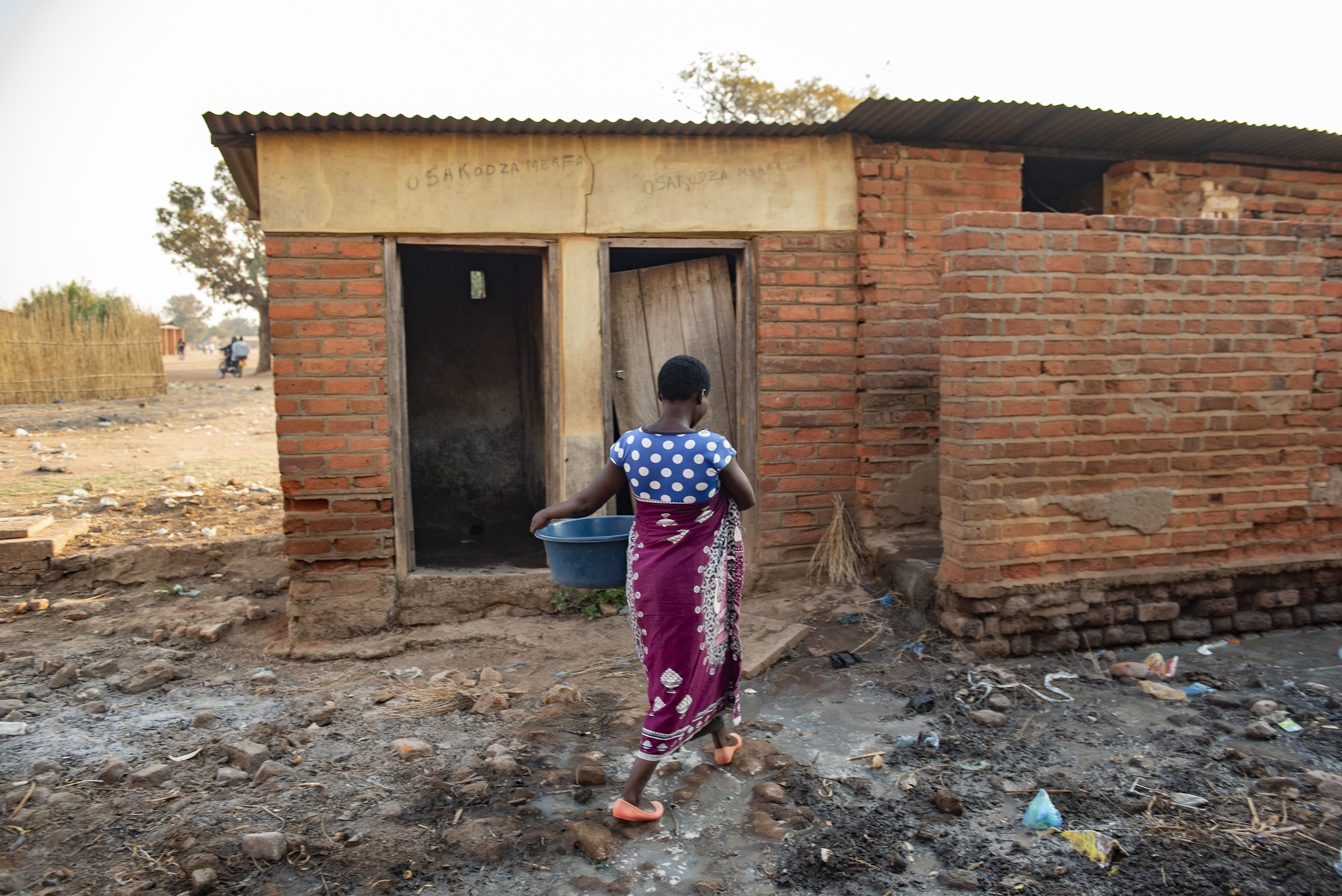 A Malawian woman makes her way through a cluttered pathway on her way to a inadequate toilet facility at a health center.