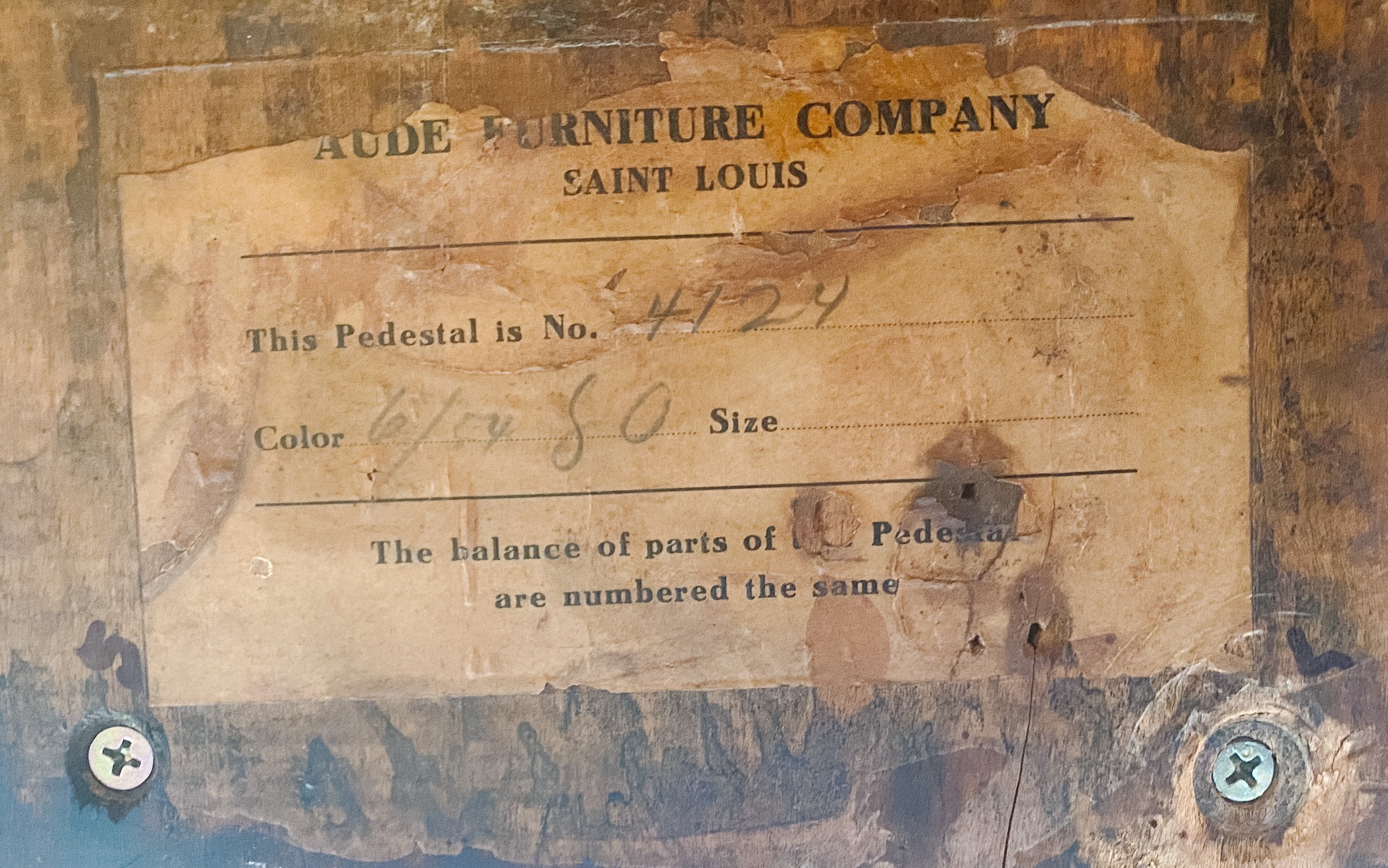 An aged, weathered paper label on a piece of furniture.