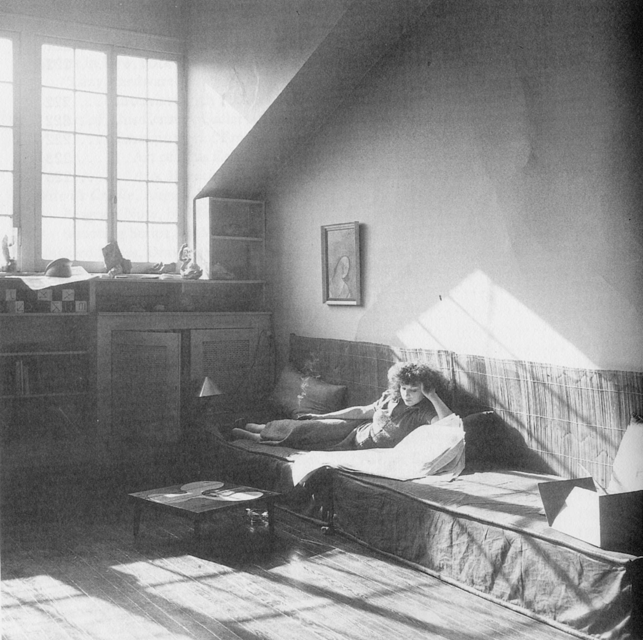 Maya Deren lounging on couch as light comes in through the window in Morton Street apartment.