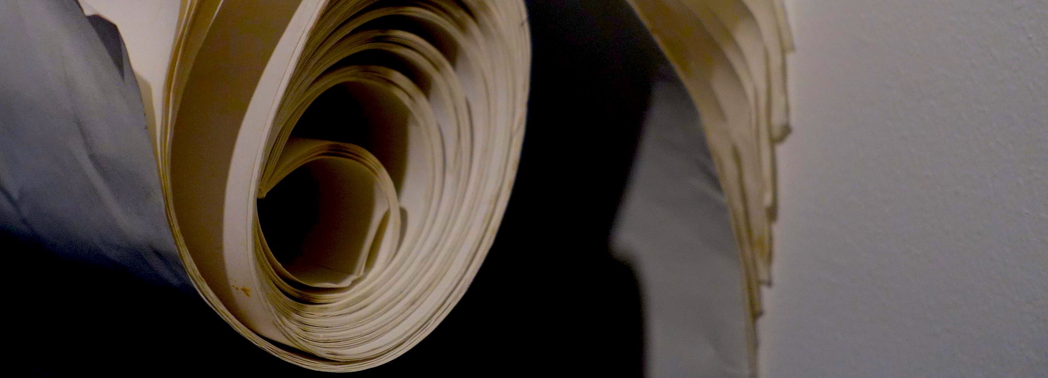 A book or bound report rolled up and allowed to unfurl