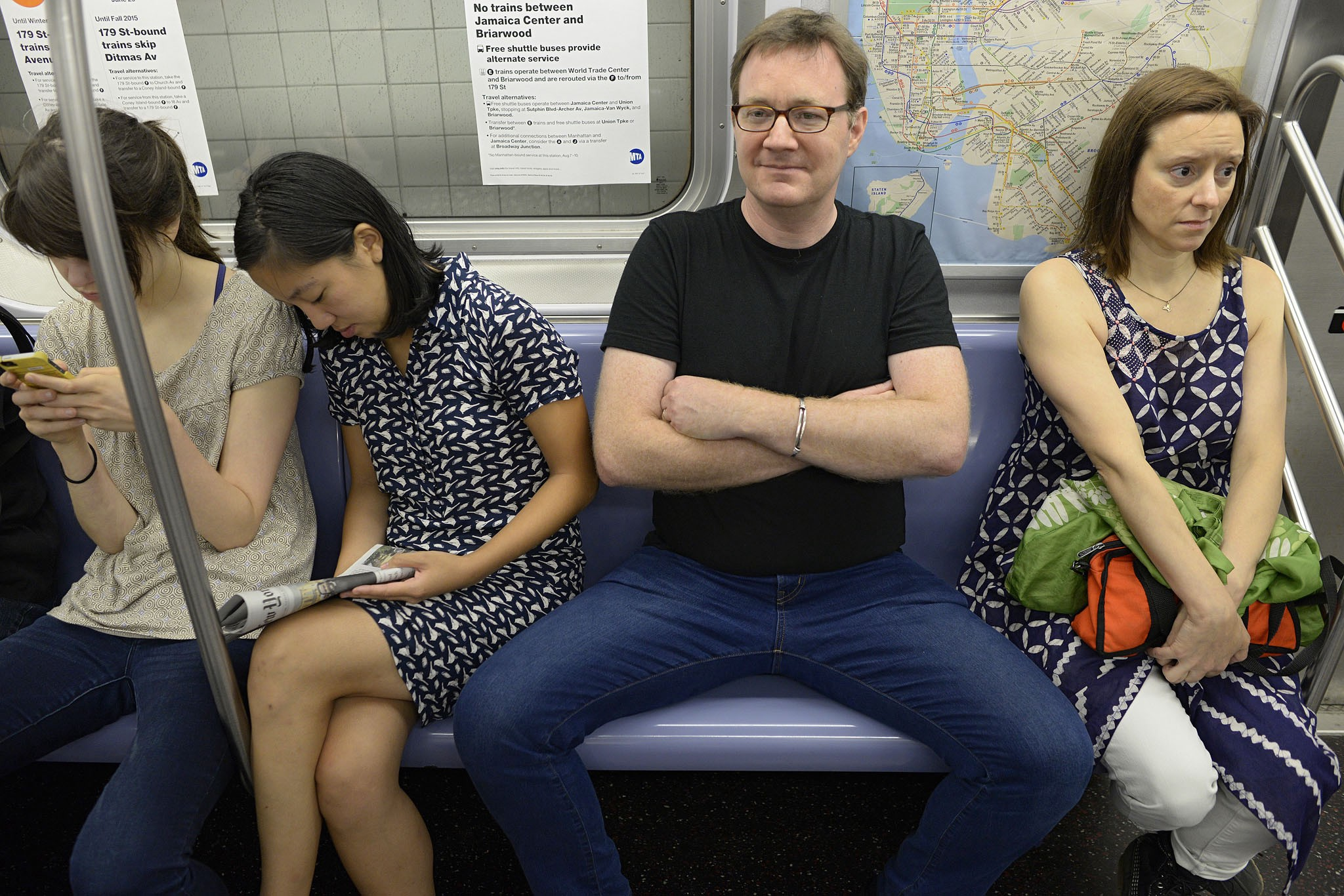 Man sitting with legs spread on the train. Women either side squashed into taking up a small space.