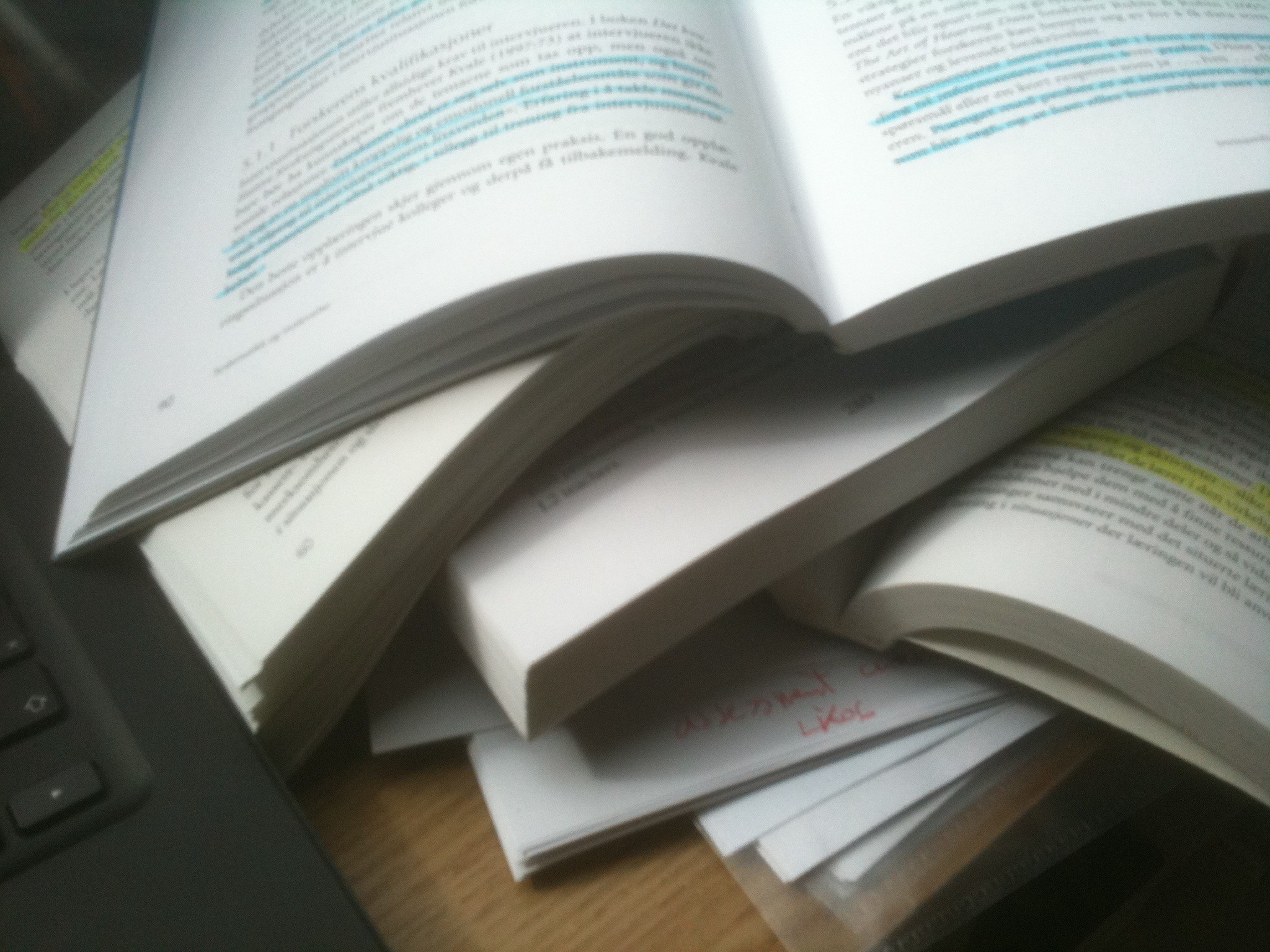 A blurry pic of a stack of opened book, sitting next to a keyboard.