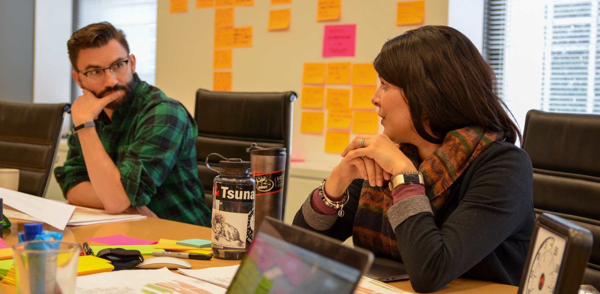 Two researchers consult with each other. The table & walls around them are covered with sticky notes.